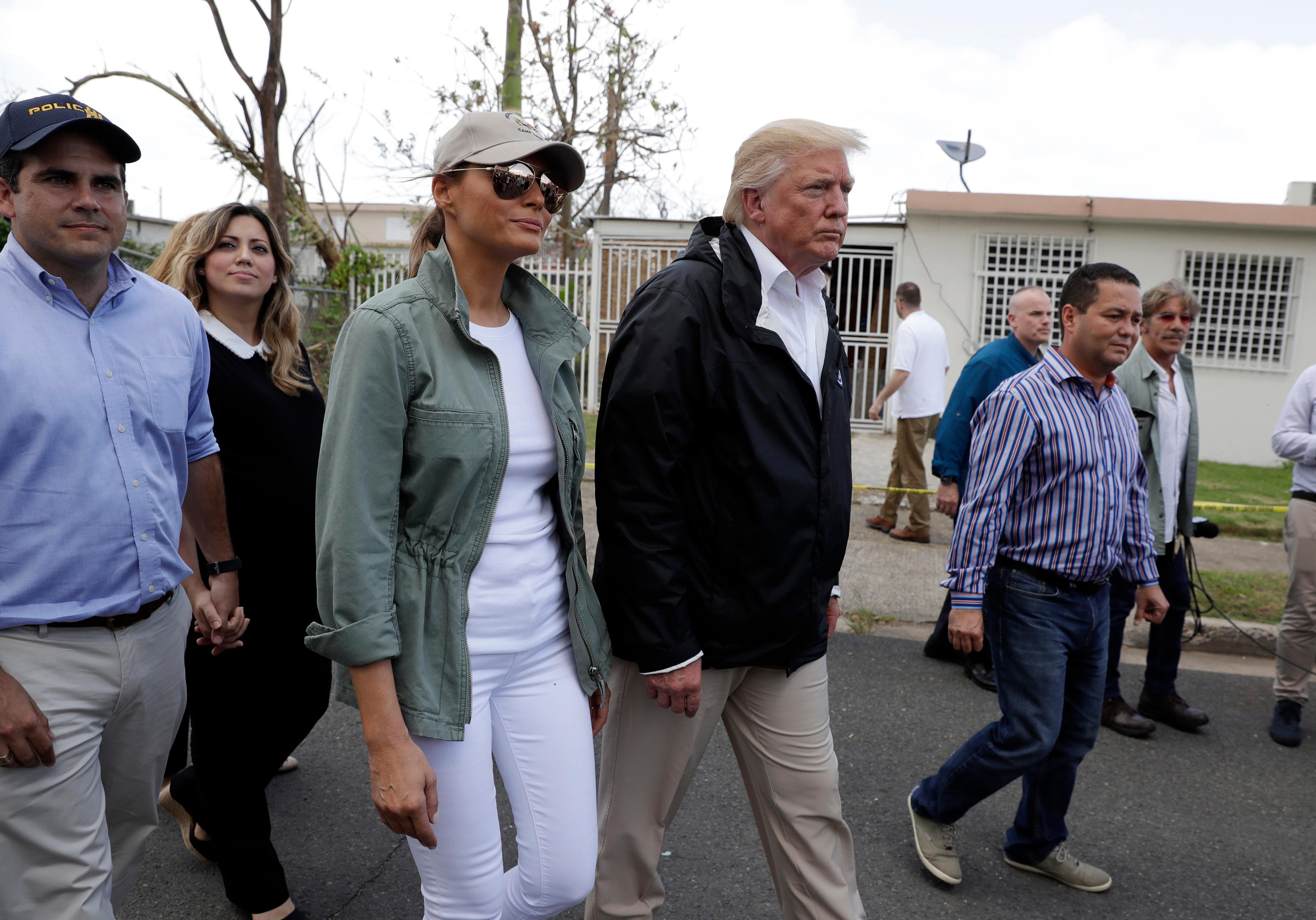 President Donald Trump and first lady Melania Trump take a walking tour with Puerto Rico Governor Ricardo Rosselló, left, and his wife Beatriz Areizaga, to survey hurricane damage and recovery efforts in a neighborhood in Guaynabo, Puerto Rico, Tuesday, Oct. 3, 2017. (AP Photo/Evan Vucci)