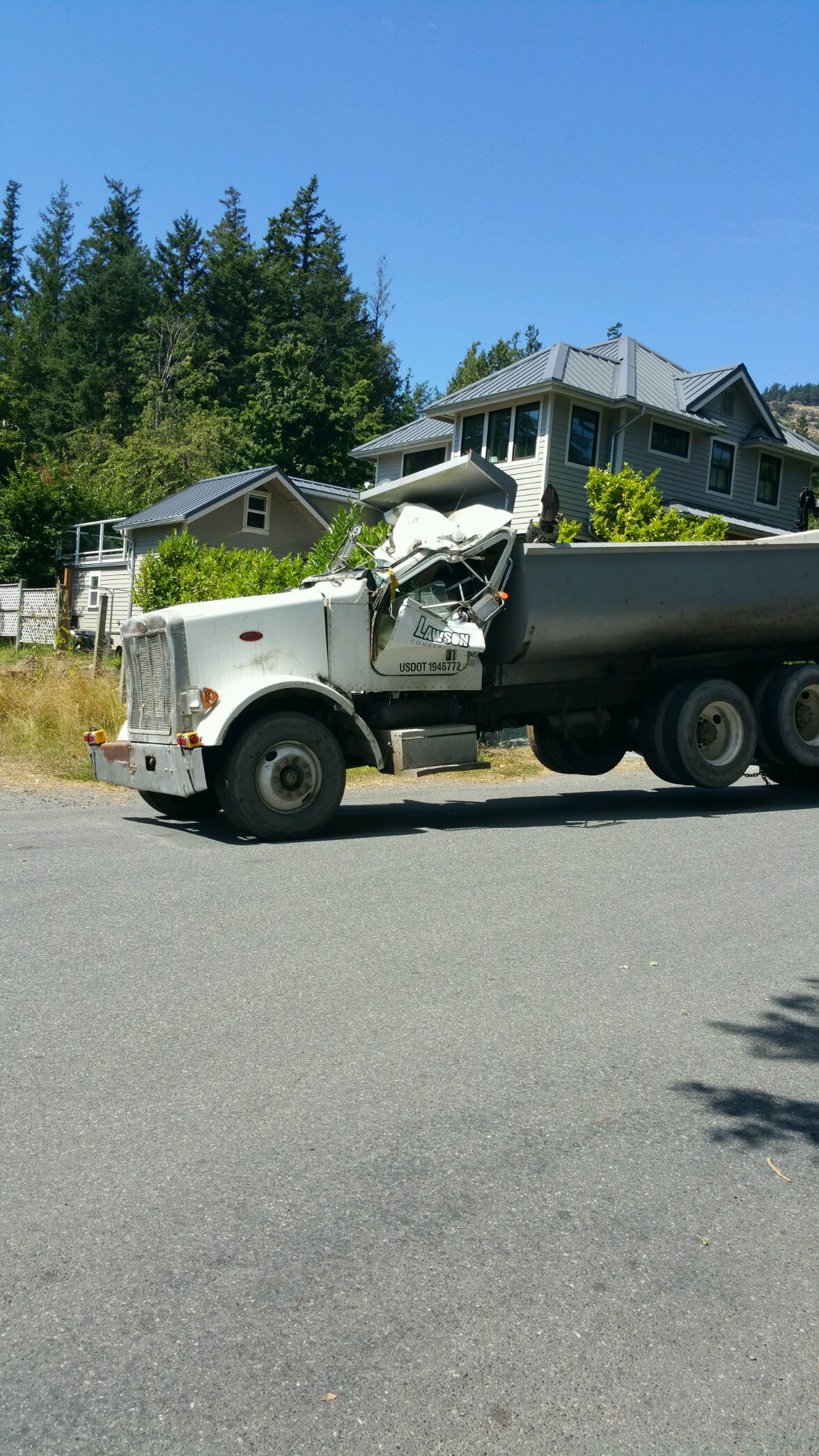 A dump truck owned by a local construction company reportedly rolled over and slid into a house Tuesday morning in the Olga area of Orcas Island, according to the San Juan County Sheriff's Office. (Photo: KOMO NEWS)