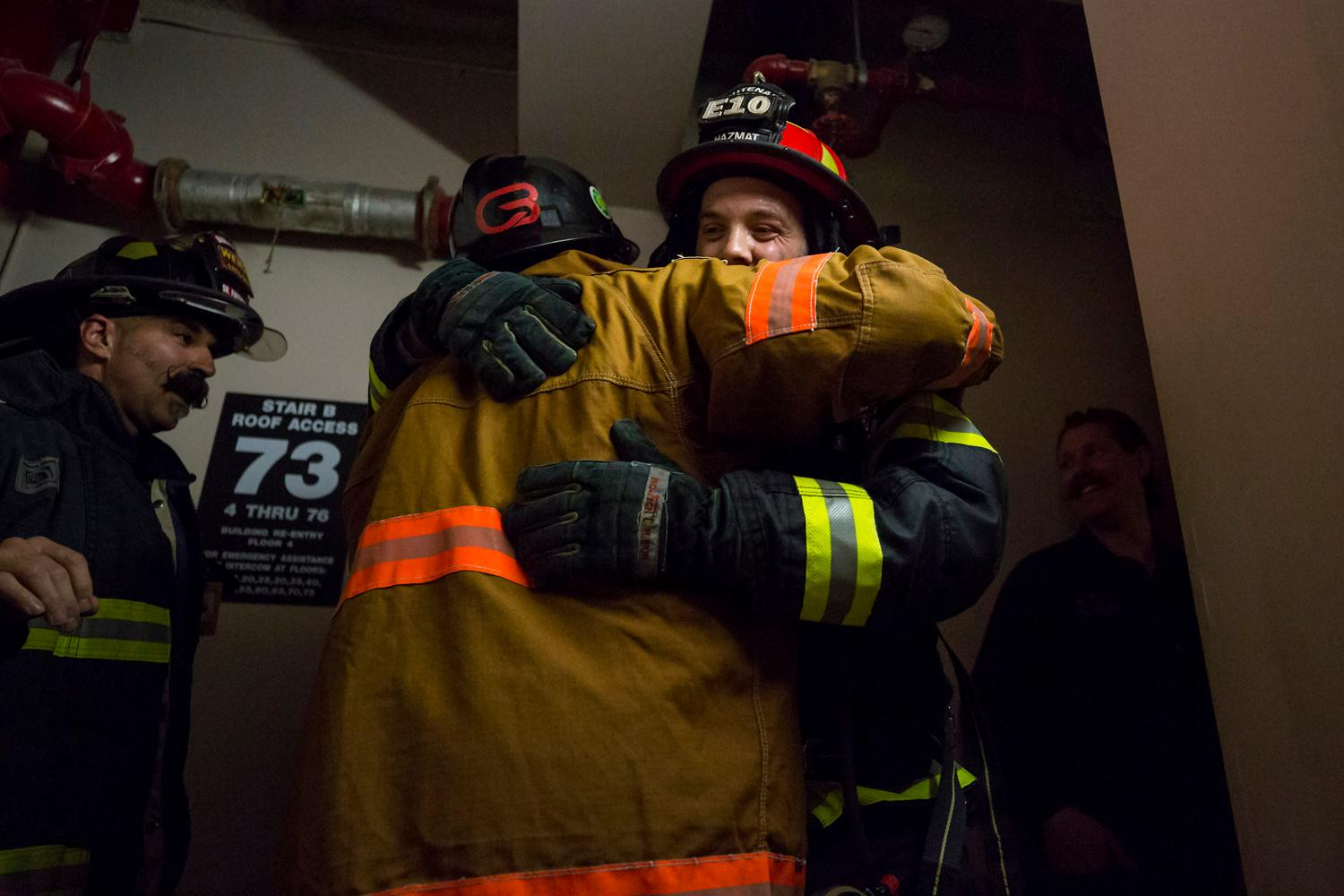 AJ from Warm 106.9 hugs Boise firefighter Rich Brown after completing a training climb up the 69 floors of the Columbia Tower Friday, March 9, 2018. 2,000 firefighters are expected the 69 floors (1,356 stairs!) on Sunday for the Scott Firefighter Stairclimb to benefit the Leukemia & Lymphoma Society. To donate to this cause, please visit www.firefighterstairclimb.org. (Sy Bean / Seattle Refined)