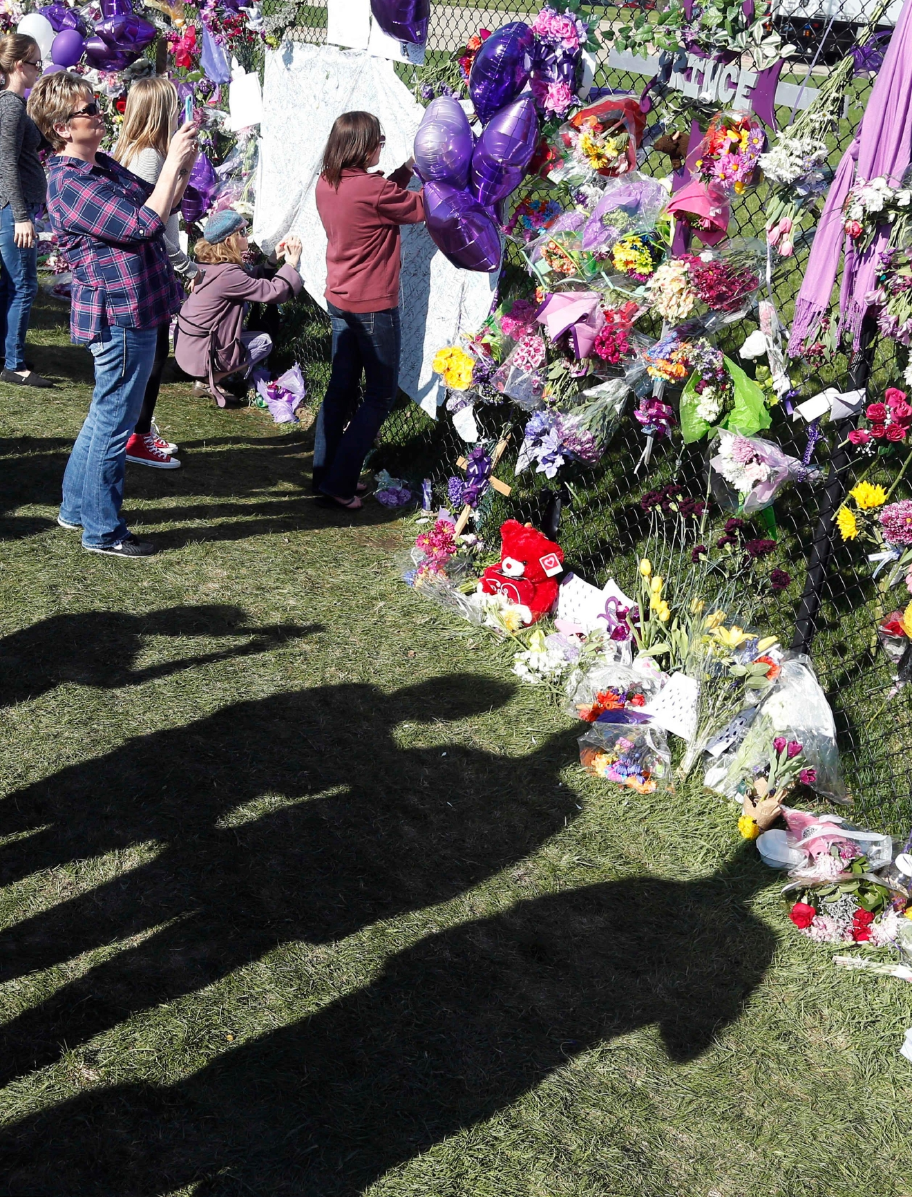The shadows of fans mark the ground along the memorial fence path in memory of pop superstar Prince at Paisley Park Studios, Friday, April 22, 2016 in Chanhassen, Minn. Prince died Thursday at Paisley Park at the age of 57. (AP Photo/Jim Mone)