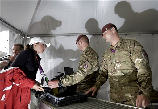 Members of the 7th Parachute Regiment Royal Horse Artillery inspect the bags of visitors as they help to provide security at the 2012 Summer Olympics.