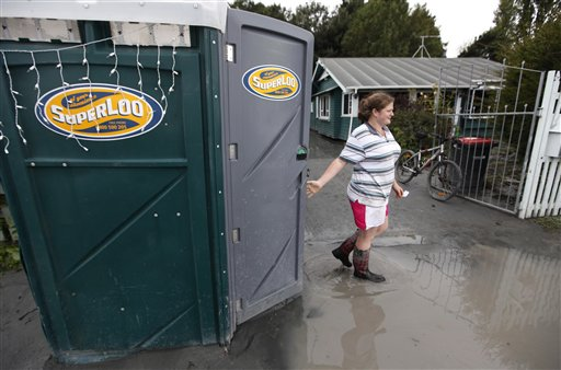 A resident walks from a portable toilet outside her home in an earthquake damaged suburb in Christchurch, New Zealand. / AP photo