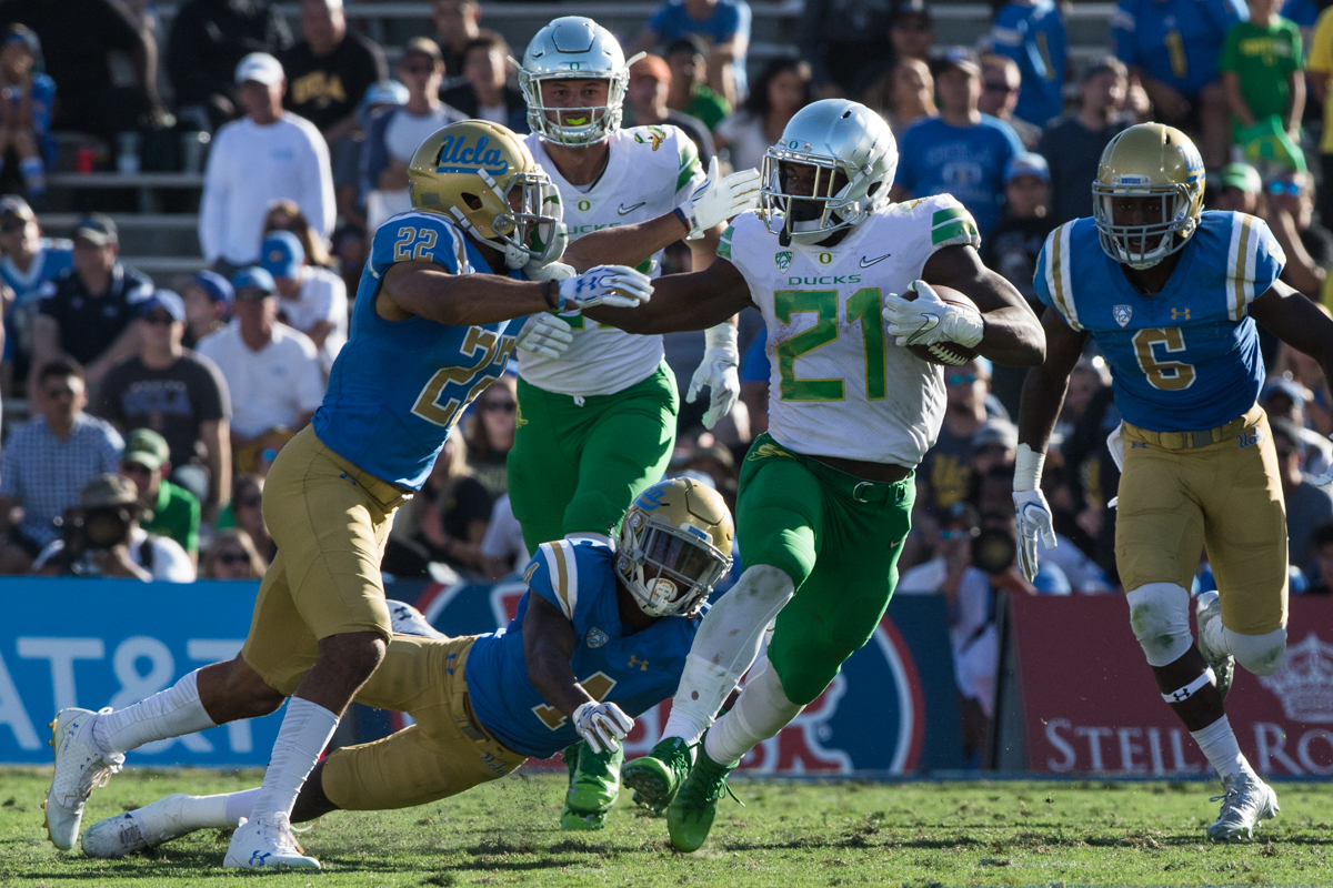 Oregon runningback Royce Freeman (#21) stiff-arms UCLA defensive back Nate Meadors (#22).  Freeman joined an elite group of NCAA running backs to surpass 5,000 career rushing yards during the game. The Oregon Ducks fell to the UCLA Bruins 14-31 after being shut out during the second half at the Rose Bowl Stadium in Pasadena, California.  This marks the third consecutive loss for the Ducks, dropping their record to 4-4 on the season.  Photo by Austin Hicks, Oregon News Lab