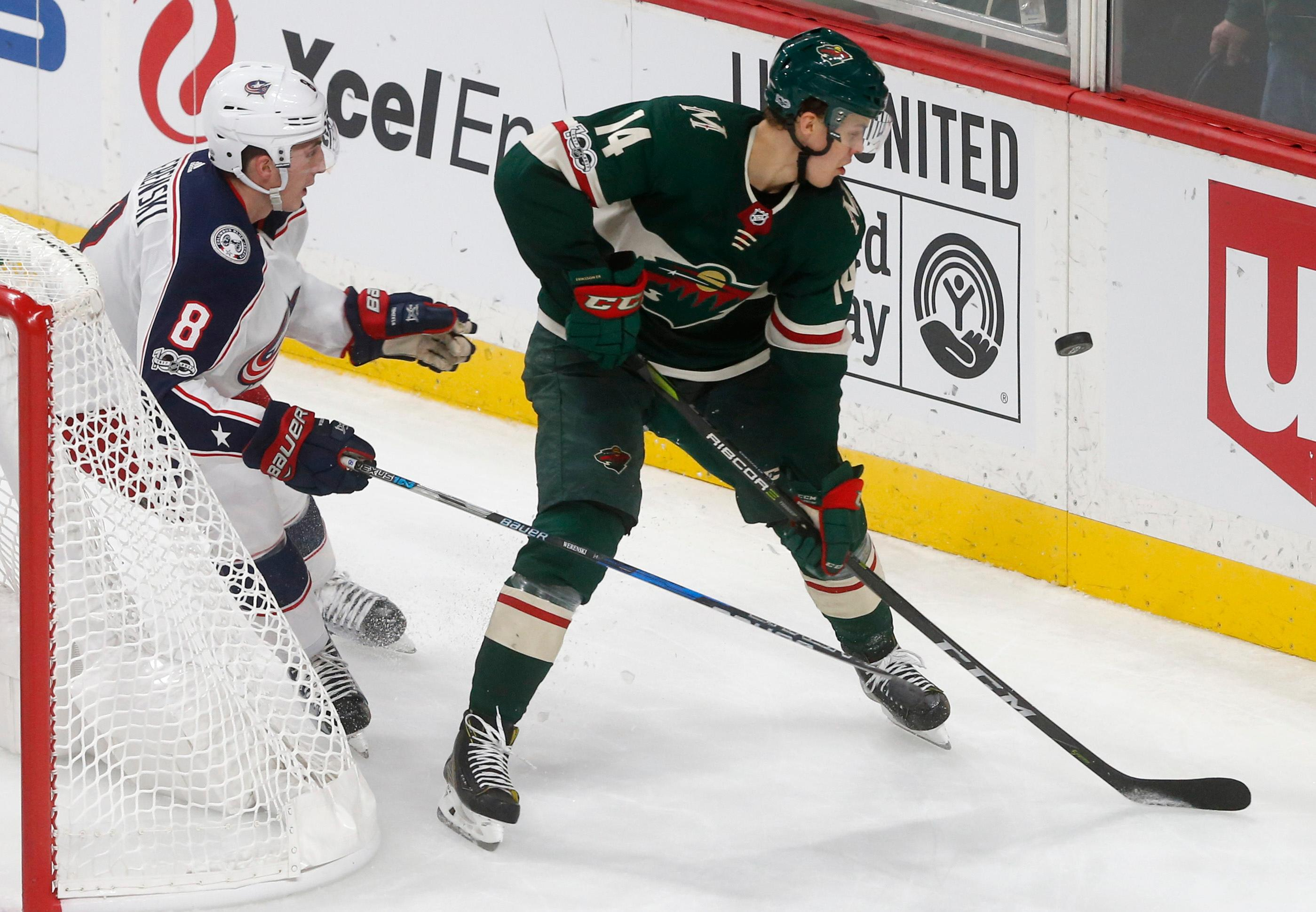 Columbus Blue Jackets' Zach Werenski, left, and Minnesota Wild's Joel Eriksson Ek of Sweden watch the puck bounce off the boards behind the net during the second period of an NHL hockey game Saturday, Oct. 14, 2017, in St. Paul, Minn. (AP Photo/Jim Mone)