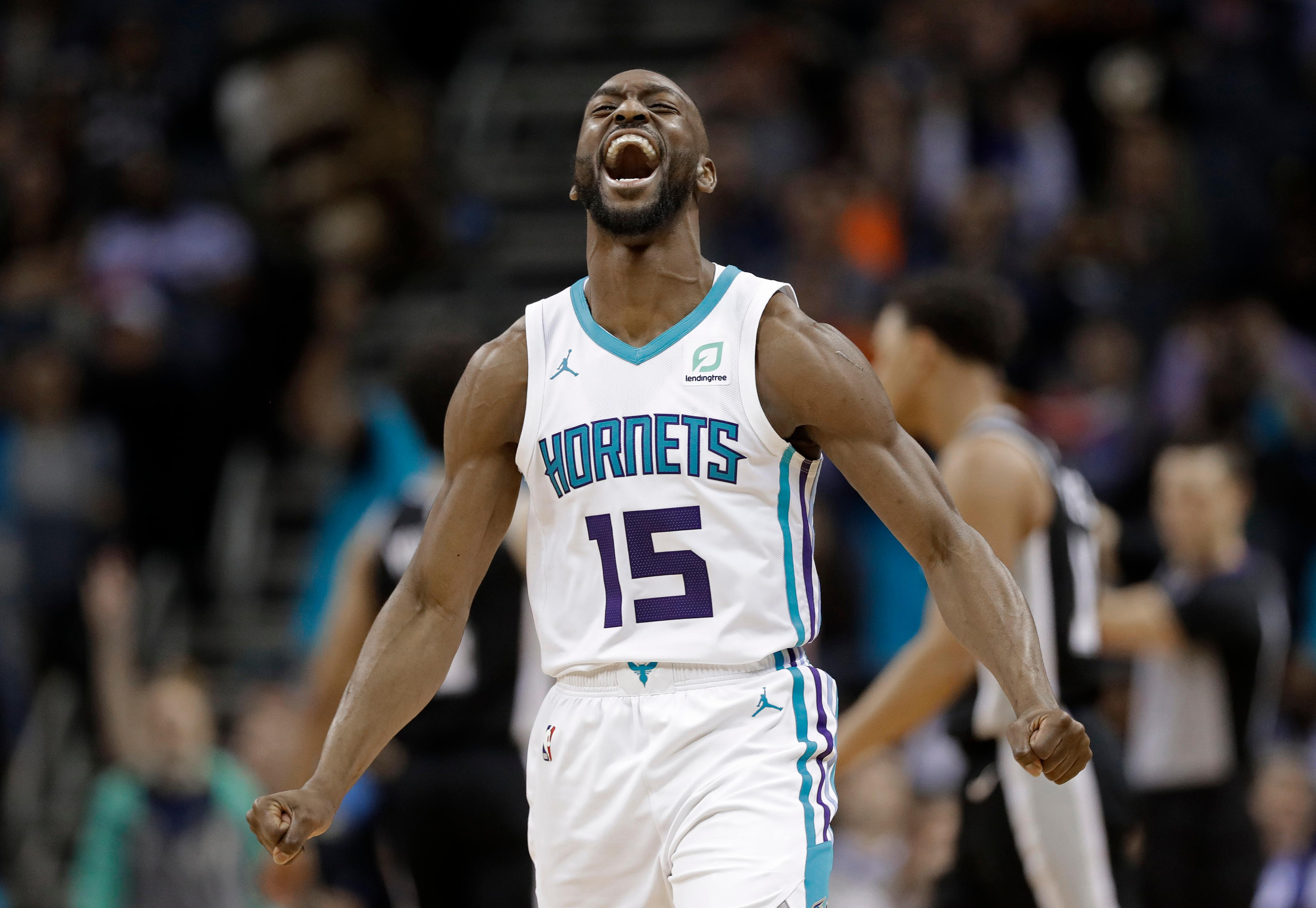 File-This March 26, 2019, file photo shows Charlotte Hornets' Kemba Walker (15) reacting after making a basket against the San Antonio Spurs during the second half of an NBA basketball game in Charlotte, N.C. A person with knowledge of the situation says Kemba Walker has told the Charlotte Hornets of his intention to sign with the Boston Celtics once the NBA's offseason moratorium ends July 6. Walker is planning to meet with the Celtics on Sunday, June 30, 2019, to discuss and likely finalize a four-year, $141 million deal, according to the person who spoke to The Associated Press on condition of anonymity because neither Walker nor the Hornets publicly revealed any details. (AP Photo/Chuck Burton, File)