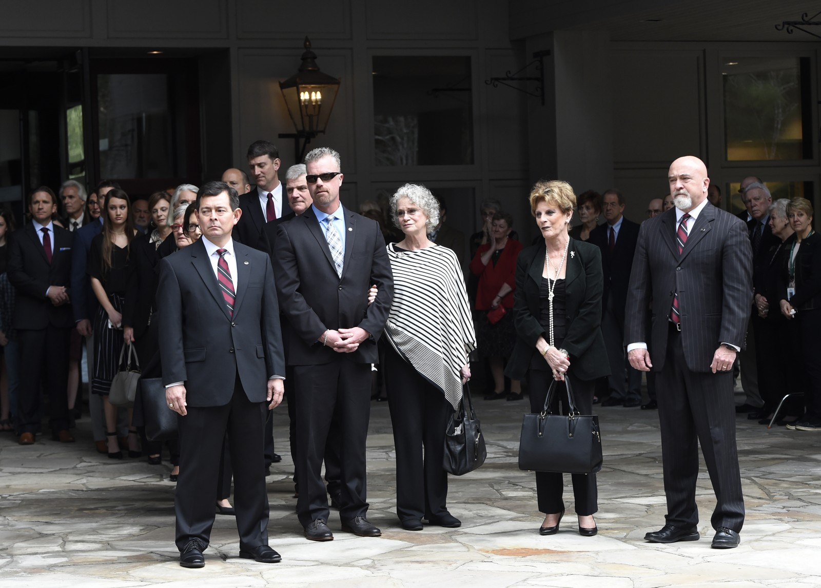 Family members look on as the body of Rev. Billy Graham is carried to the hearse to leave the Billy Graham Training Center at the Cove on Saturday, Feb. 24, 2018, in Asheville, N.C. Graham's body will be brought to his hometown of Charlotte on Saturday, Feb. 24, as part of a procession expected to draw crowds of well-wishers. (Kathy Kmonicek/pool photo)