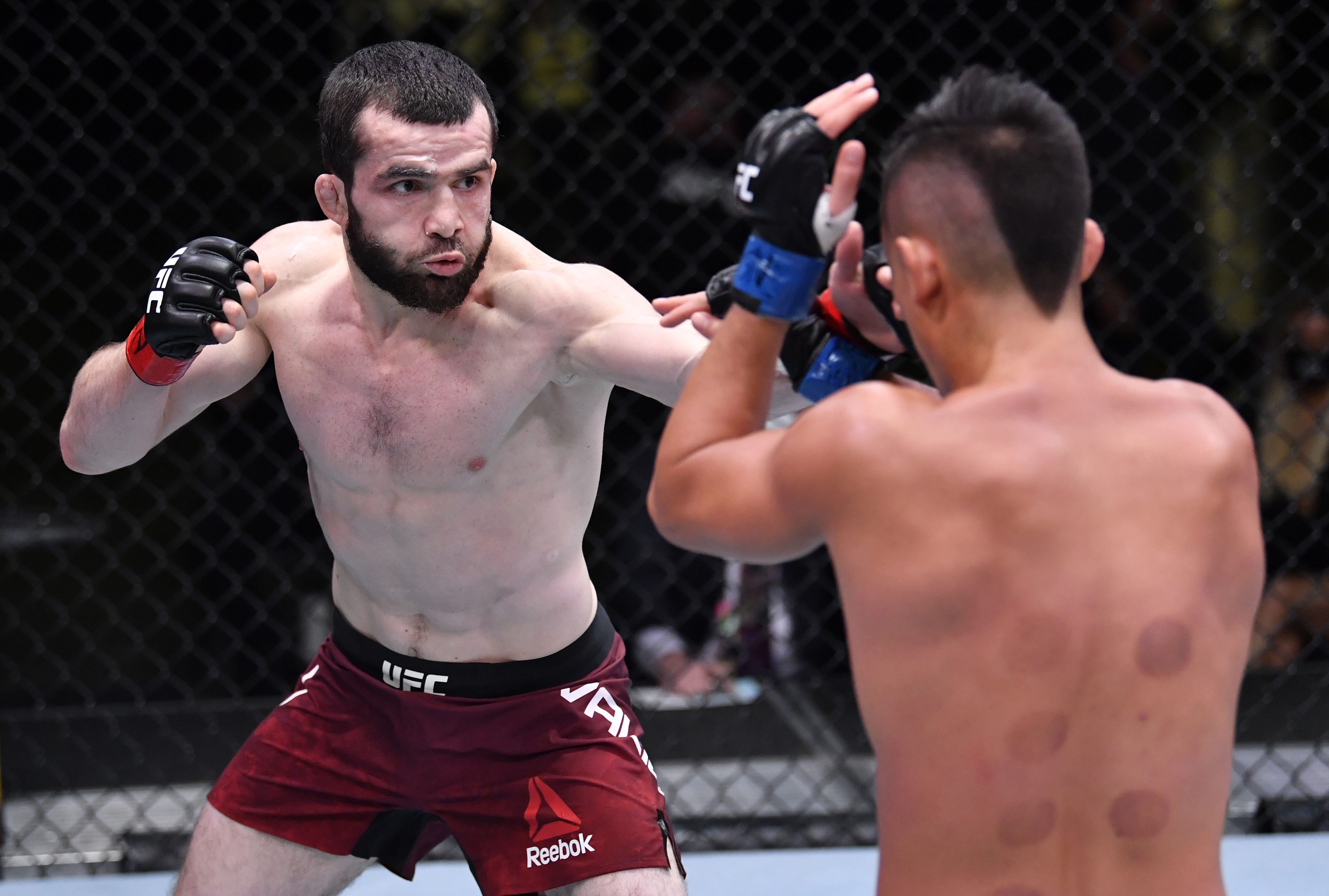 LAS VEGAS, NEVADA - FEBRUARY 06: In this handout image provided by UFC, (L-R) Timur Valiev of Russia punches Martin Day in their featherweight fight during the UFC Fight Night event at UFC APEX on February 06, 2021 in Las Vegas, Nevada. (Photo by Chris Unger/Zuffa LLC via Getty Images)