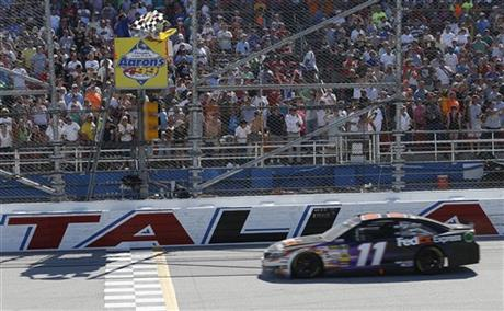 Denny Hamlin (11) takes the checkered flag under caution during the NASCAR Aaron's 499 Sprint Cup series auto race at Talladega Superspeedway, Sunday, May 4, 2014, in Talladega, Ala. (AP Photo/John Bazemore)