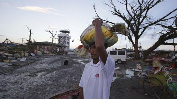 A survivor carries relief goods amongst the devastation after powerful Typhoon Haiyan slammed into Tacloban city, Leyte province central Philippines.