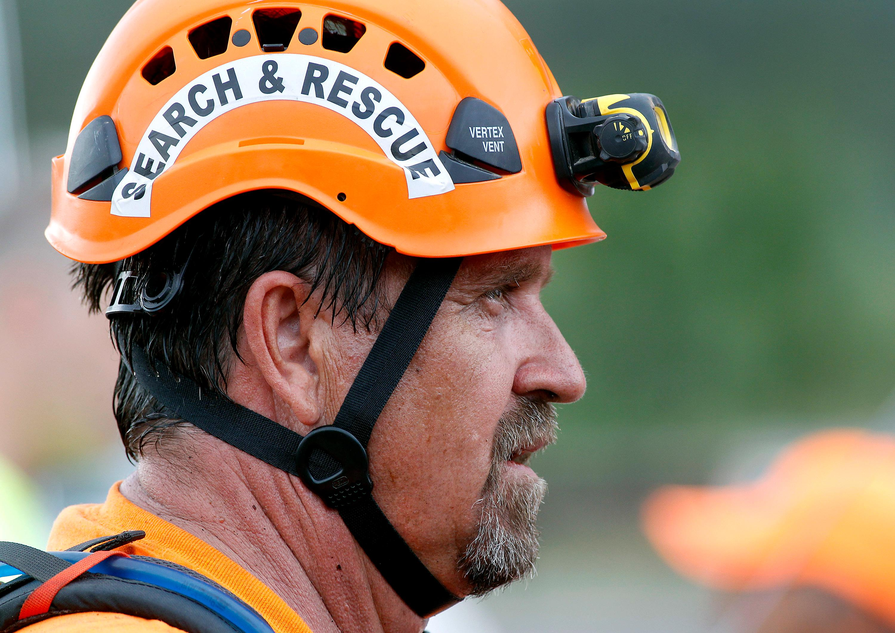 Brad Cole, of the Tonto Rim Search and Rescue, listens during a briefing at the Gila County Sheriff's Office command center during a search operation for victims of a flash flood along the banks of the East Verde River, Sunday, July 16, 2017, in Payson, Ariz. Search and rescue crews, including 40 people on foot and others in a helicopter, have recovered bodies of children and adults, some as far as two miles down the river after Saturday's flash flooding poured over a popular swimming area inside the Tonto National Forest in central Arizona. (AP Photo/Ralph Freso)