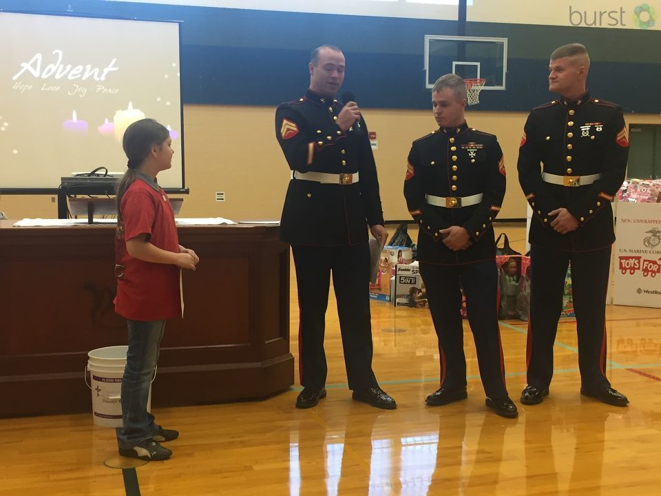 Three uniformed Marines were on hand at Peace Lutheran School, picking up toys collected by 9-year-old Michaela Witgen. (Photo Credit: Mike Horne)