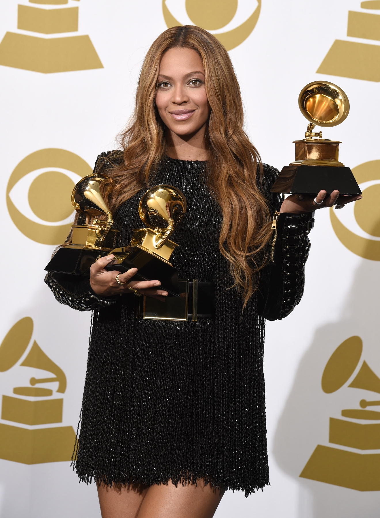 Beyoncé poses with three of her trophies in the press room of the Grammy Awards ceremony in Los Angeles on Feb. 8, 2015. (Photo credit: Chris Pizzello/Invision/AP.)