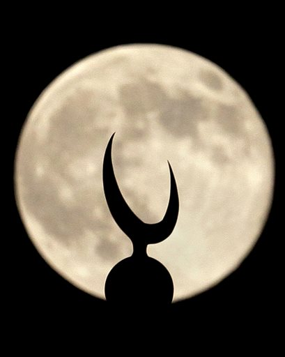 A perigee moon, also known as a supermoon, looks over a crescent of a minaret of grand Faisal mosque in Islamabad, Pakistan,Saturday, July 12, 2014.