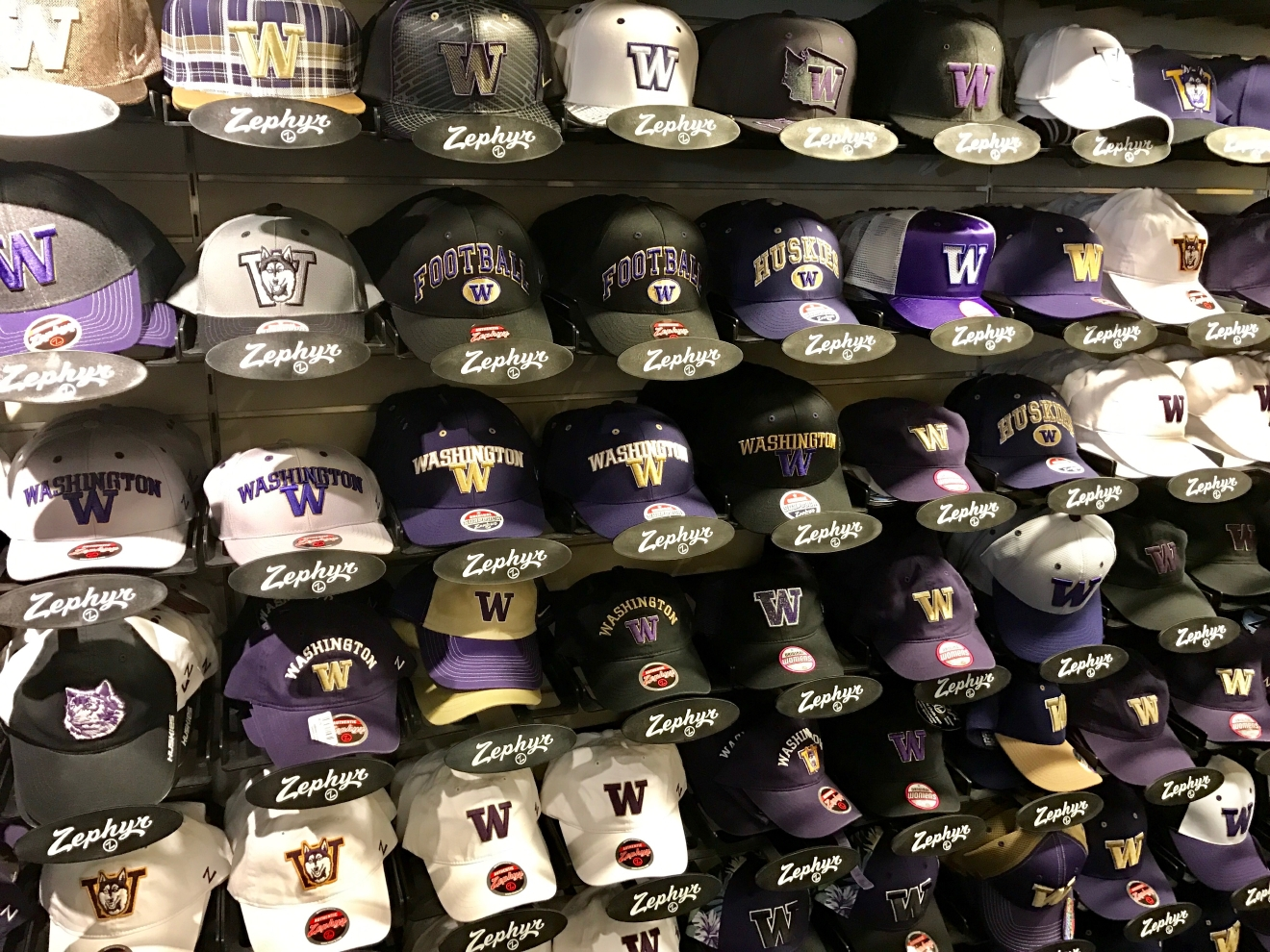 All the hats you could possibly ever want.                                          Whether you're a current student, alum, or just *love* the Dawgs, it's a pretty exciting time to be a Husky fan right now. Just to catch you up, the University of Washington football team is having one of their best seasons in years, and will be playing the Peach Bowl in Atlanta on December 31st. If you know a Dawg fan, they're probably salivating at the mouth right about now. Which is why it's a perfect time to give them a themed gift! Here are some of the coolest Husky gear we saw at the University Bookstore on the Avenue during our last visit. Pro Tip: They're open 10 a.m. - 7 p.m. on Christmas Eve! (Image: Britt Thorson / Seattle Refined)