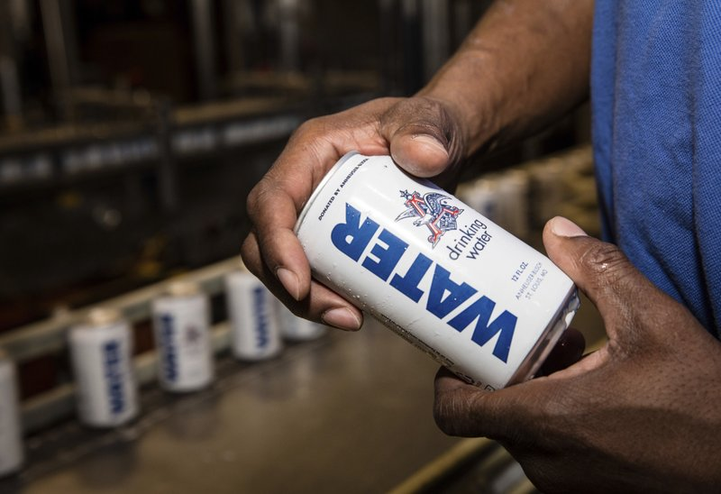 In this undated photo provided by Anheuser-Busch a man shows a canned water in Cartersville, Ga. The brewery is shipping canned drinking water to the American Red Cross to help Hurricane Harvey relief efforts in Texas and Louisiana. (Anheuser-Busch via AP)
