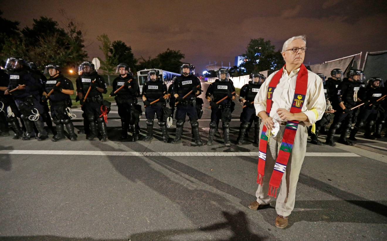 A member of the clergy stands in front of a line of police officers in Charlotte, N.C. Thursday, Sept. 22, 2016. blocking the access road to I-277 on the third night of protests following Tuesday's fatal police shooting of Keith Lamont Scott. (AP Photo/Chuck Burton)