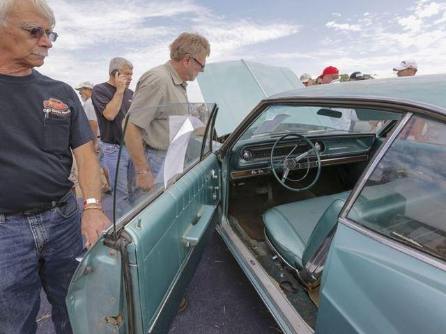 Potential bidders look over a 1965 Chevrolet Impala 2 door hardtop to be sold in the auction of vintage cars and trucks from the former Lambrecht Chevrolet dealership in Pierce, Neb.
