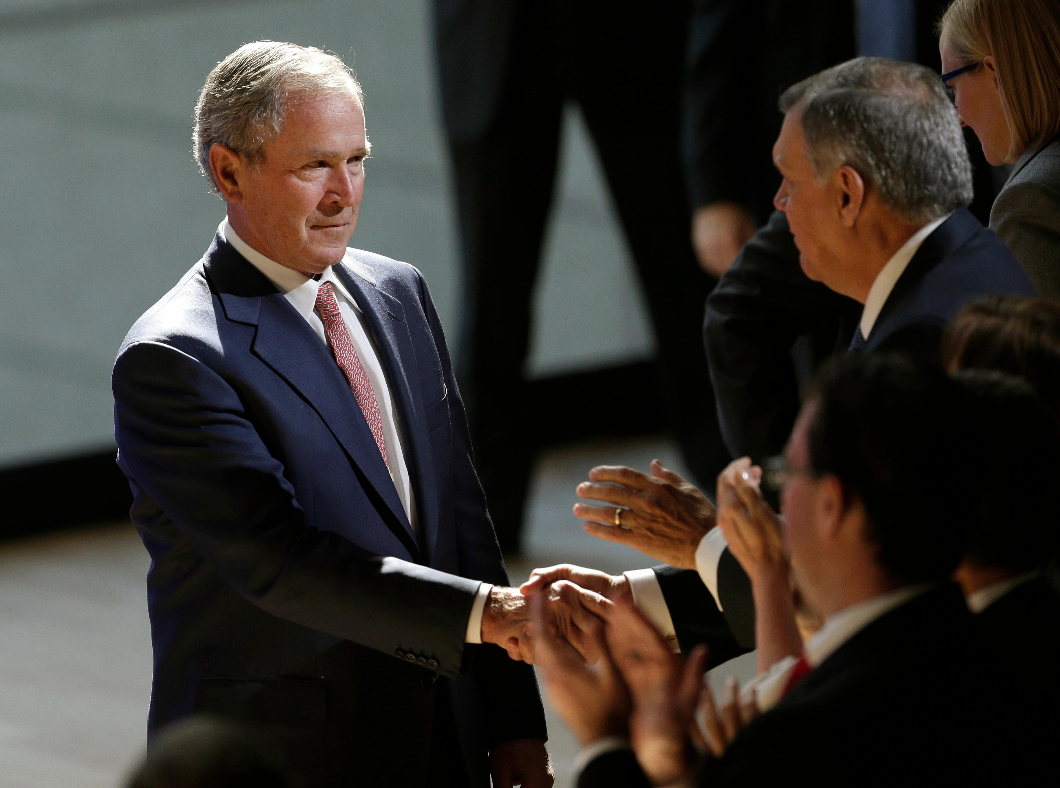 Former U.S. President George W. Bush shakes hands with audience members after speaking at a forum sponsored by the George W. Bush Institute in New York, Thursday, Oct. 19, 2017. (AP Photo/Seth Wenig)
