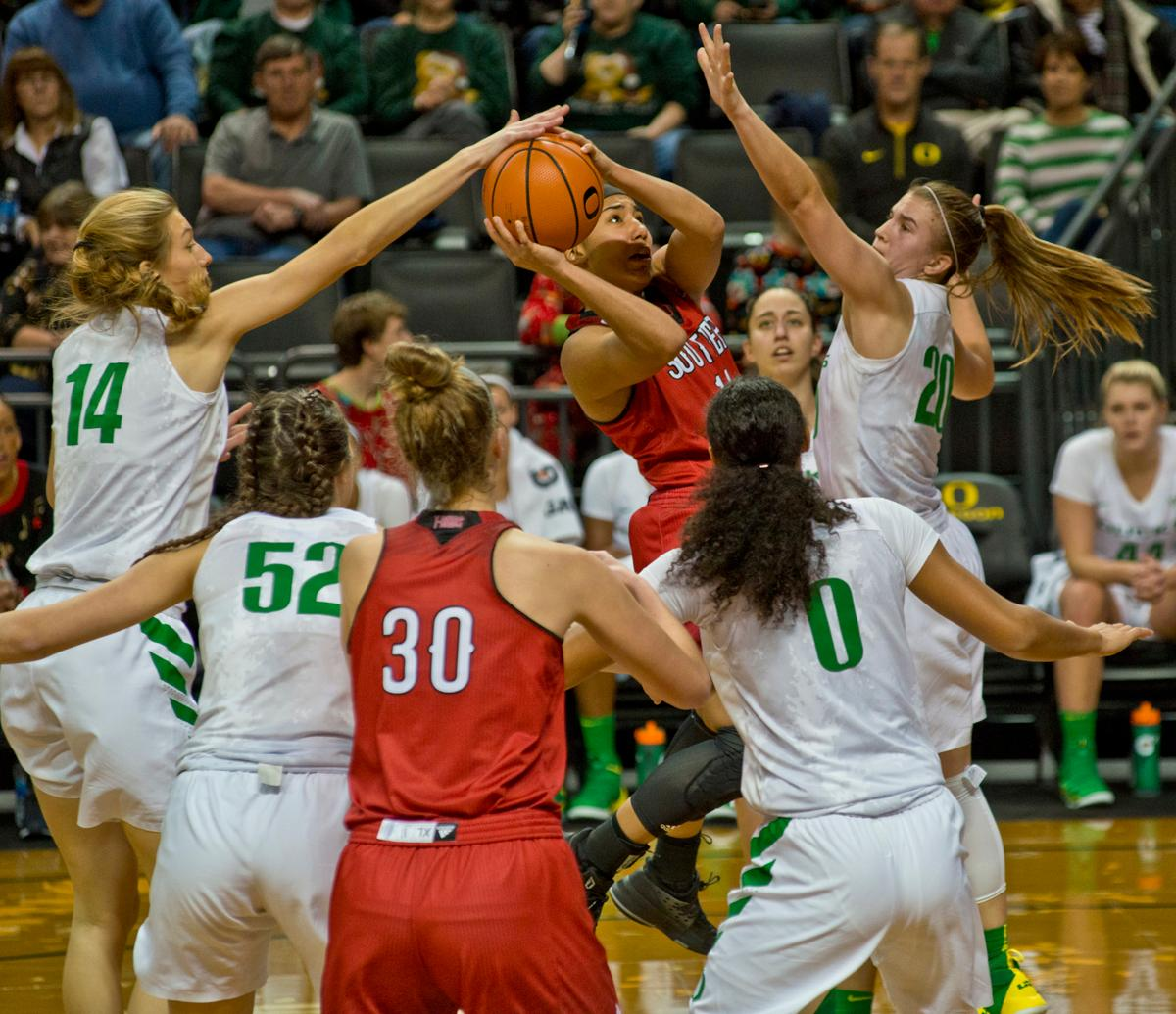 Oregon Ducks Lydia Giomi (#14, white jersey) blocks the shot of Southern Utah Thunderbirds Breanu Reid (#14, red jersey with ball) as the Ducks defense cuts Reid off from the basket. The University of Oregon Ducks women basketball team defeated the Southern Utah Thunderbirds 98-38 in Matthew Knight Arena Saturday afternoon. The Ducks had four players in double-digits: Ruthy Hebard with 13; Mallory McGwire with 10; Lexi Bando with 17 which included four three-pointers; and Sabrina Ionescu with 16 points. The Ducks overwhelmed the Thunderbirds, shooting 50% in field goals to South Utah's 26.8%, 53.8% in three-pointers to 12.5%, and 85.7% in free throws to 50%. The Ducks, with an overall record of 8-1, and coming into this game ranked 9th, will play their next home game against Ole Miss on December 17. Photo by Dan Morrison, Oregon News Lab