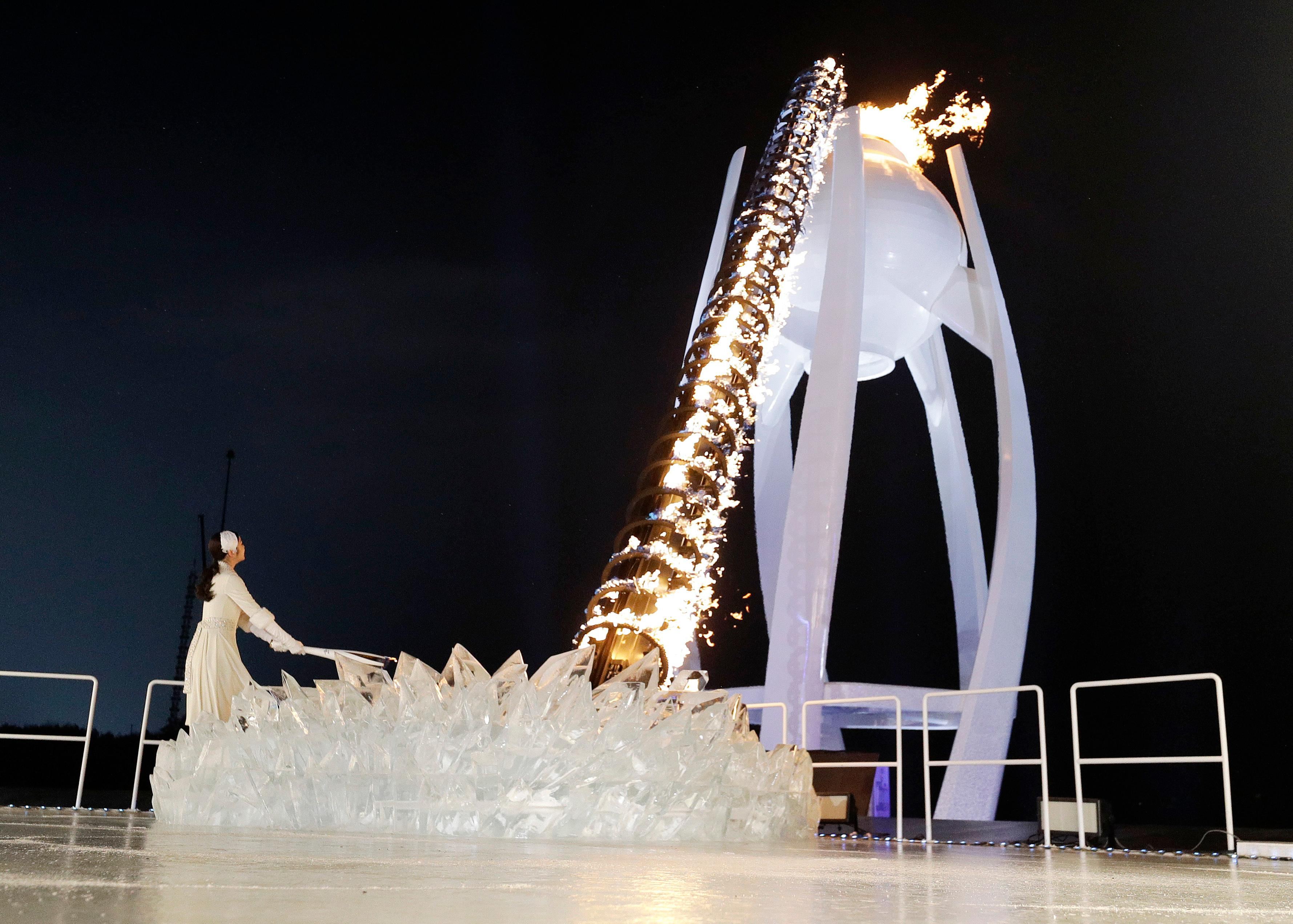 A torchbearer lights the Olympic flame during the opening ceremony of the 2018 Winter Olympics in Pyeongchang, South Korea, Friday, Feb. 9, 2018. (AP Photo/David J. Phillip,Pool)