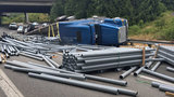 Semi truck overturns, dumps load of pipes under I-5 in Tukwila