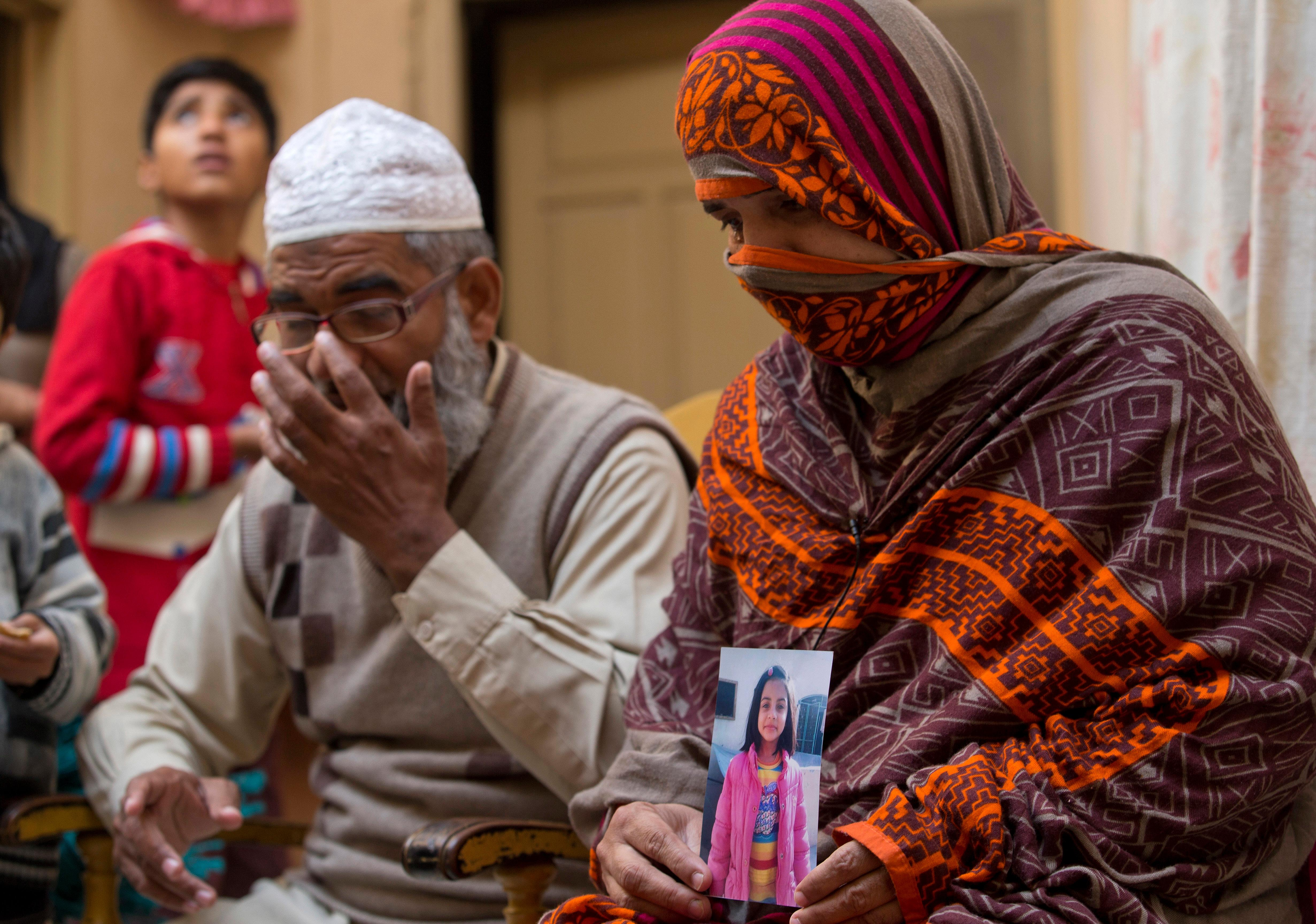 In this  Jan. 18, 2018, file photo, Nusrat holds a picture of her daughter Zainab Ansari with her husband Mohammed Amin Ansari, left, in Kasur, Pakistan. (AP Photo/B.K. Bangash, File)