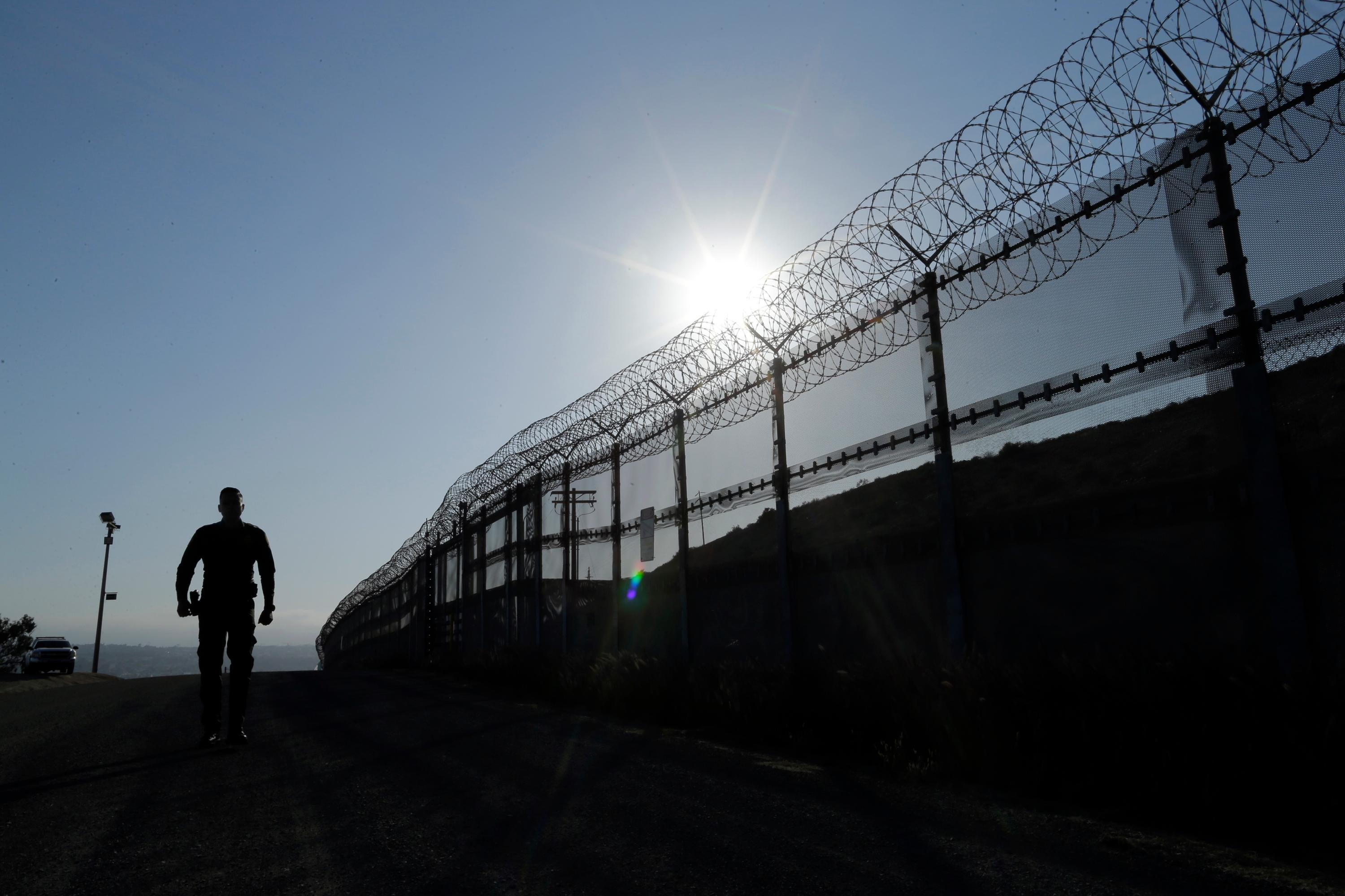 FILE - In this June 22, 2016 file photo, a Border Patrol agent walks along a border structure in San Diego, Calif. The Trump administration has proposed spending $18 billion over 10 years to significantly extend the border wall with Mexico.{&amp;nbsp;} (AP Photo/Gregory Bull, File)<p></p>