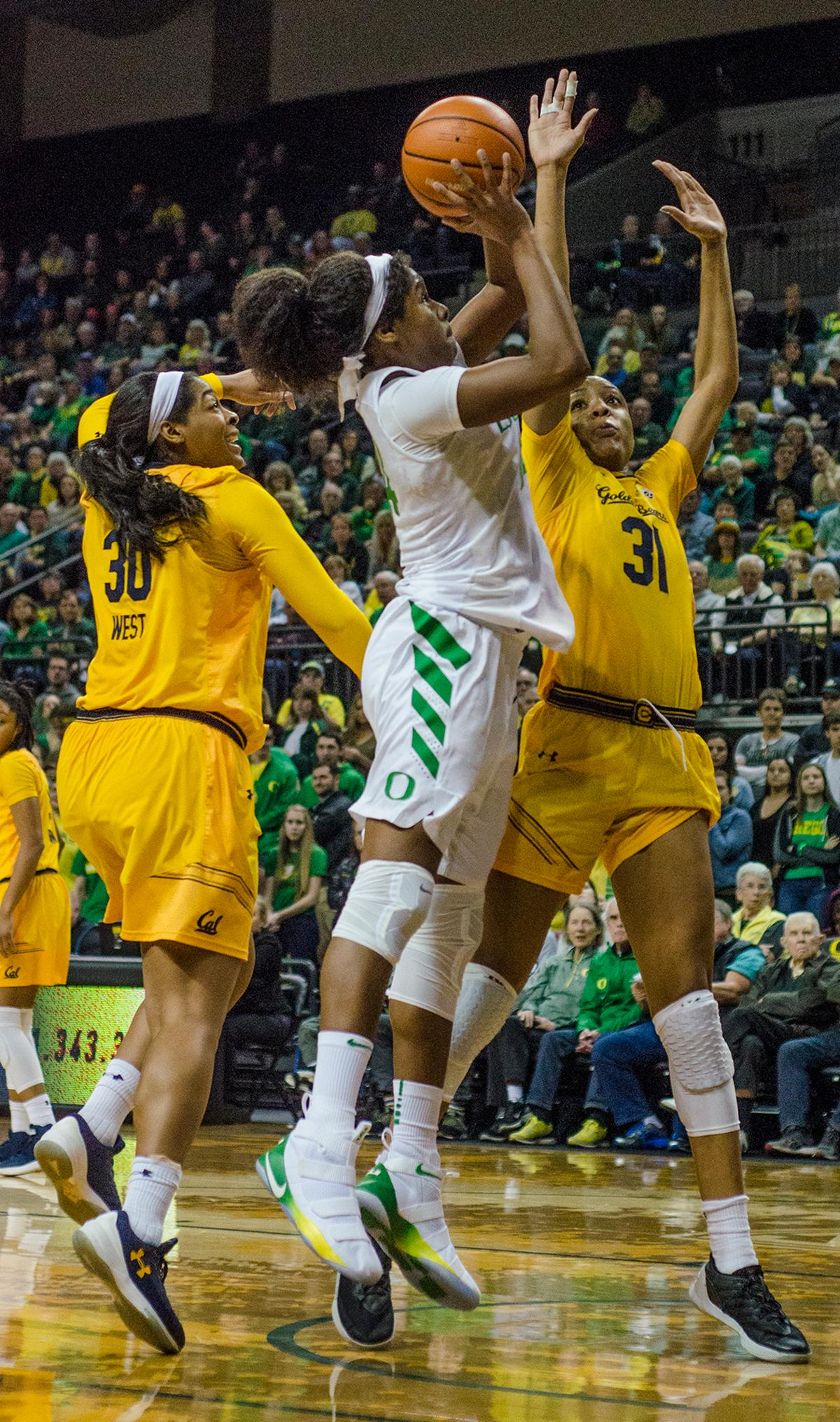 Ruthy Hebard (#24) goes up for a layup against Cal Bears CJ West (#30) and Kristine Anigwe (31). The Oregon Ducks women defeated the Cal Bears 91-54 in Matthew Knight Arena Saturday evening. The Ducks had three players in double digits: Sabrina Ionescu with 28 points; Ruthy Hebard with 18 points; and Satou Sabally with 10 points. The Ducks now stand at 10-1 in conference play and Cal drops to 6-5. Photo by Emily Gonzalez, Oregon News Lab