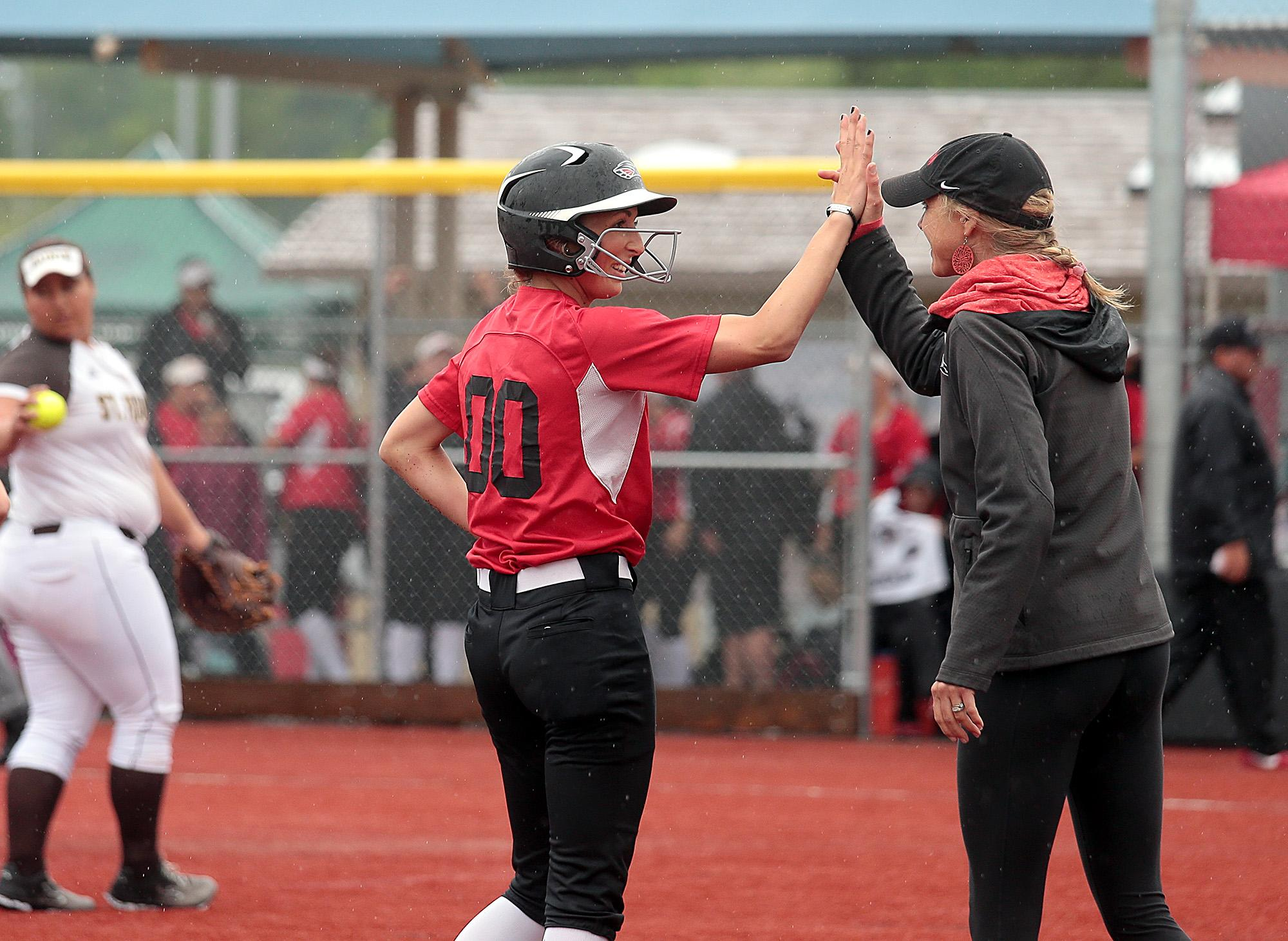 Southern Oregon University freshman Hannah Shimek gets a High-Five from Head Coach Jessica Pistole during the second game against St. Francis at US Cellular Community Park on Wednesday.[PHOTO BY:  LARRY STAUTH JR]