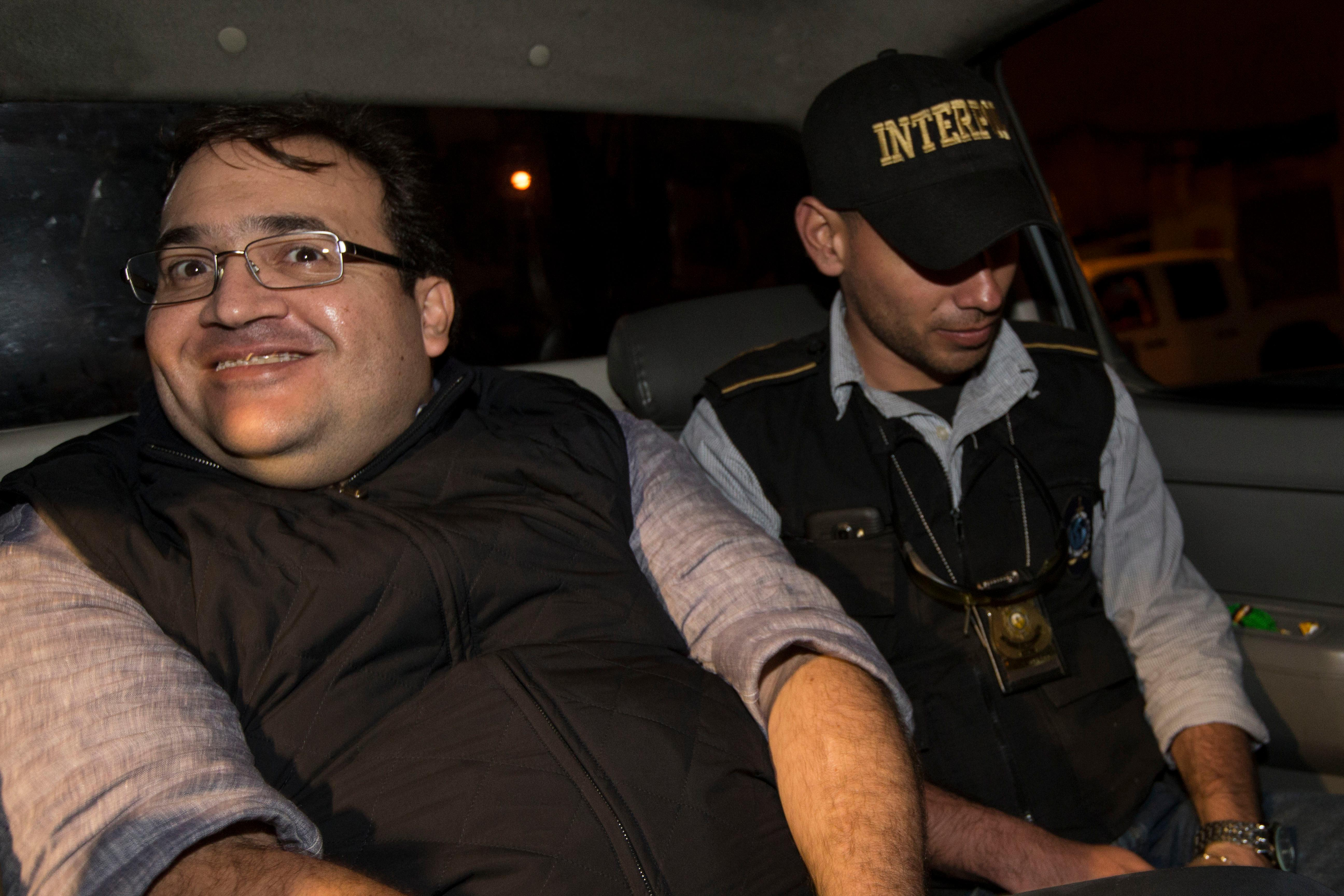 Mexico's former Veracruz state Gov. Javier Duarte, left, is escorted by an agent of the local Interpol office inside a police car as they arrive at Guatemala City, early Sunday, April 16, 2017. Duarte, who is accused of running a ring that allegedly pilfered from state coffers, has been detained in Guatemala after six months as a fugitive and a high-profile symbol of government corruption. (AP Photo/Moises Castillo)