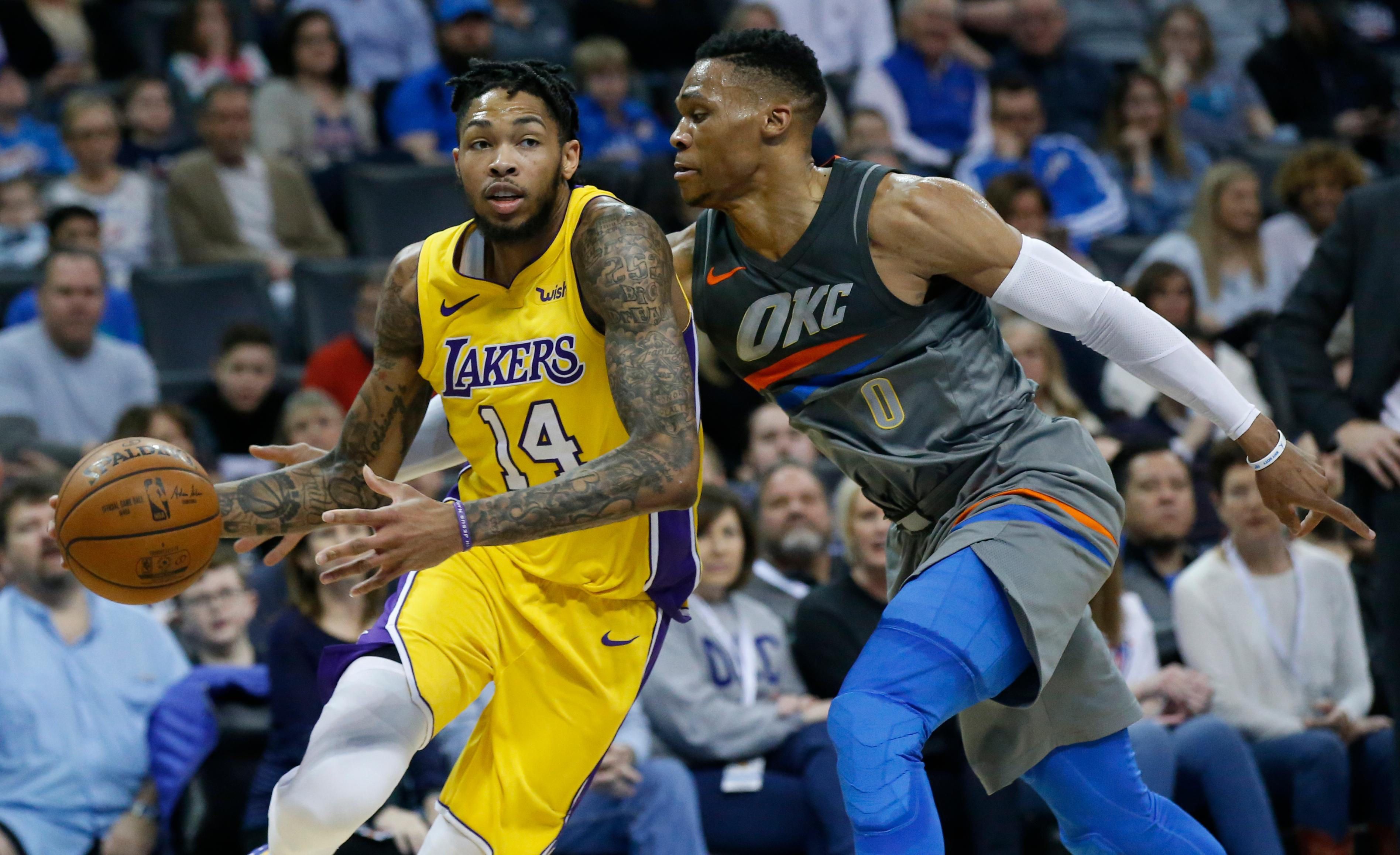 Los Angeles Lakers forward Brandon Ingram (14) drives around Oklahoma City Thunder guard Russell Westbrook (0) in the first half of an NBA basketball game in Oklahoma City, Sunday, Feb. 4, 2018. (AP Photo/Sue Ogrocki)