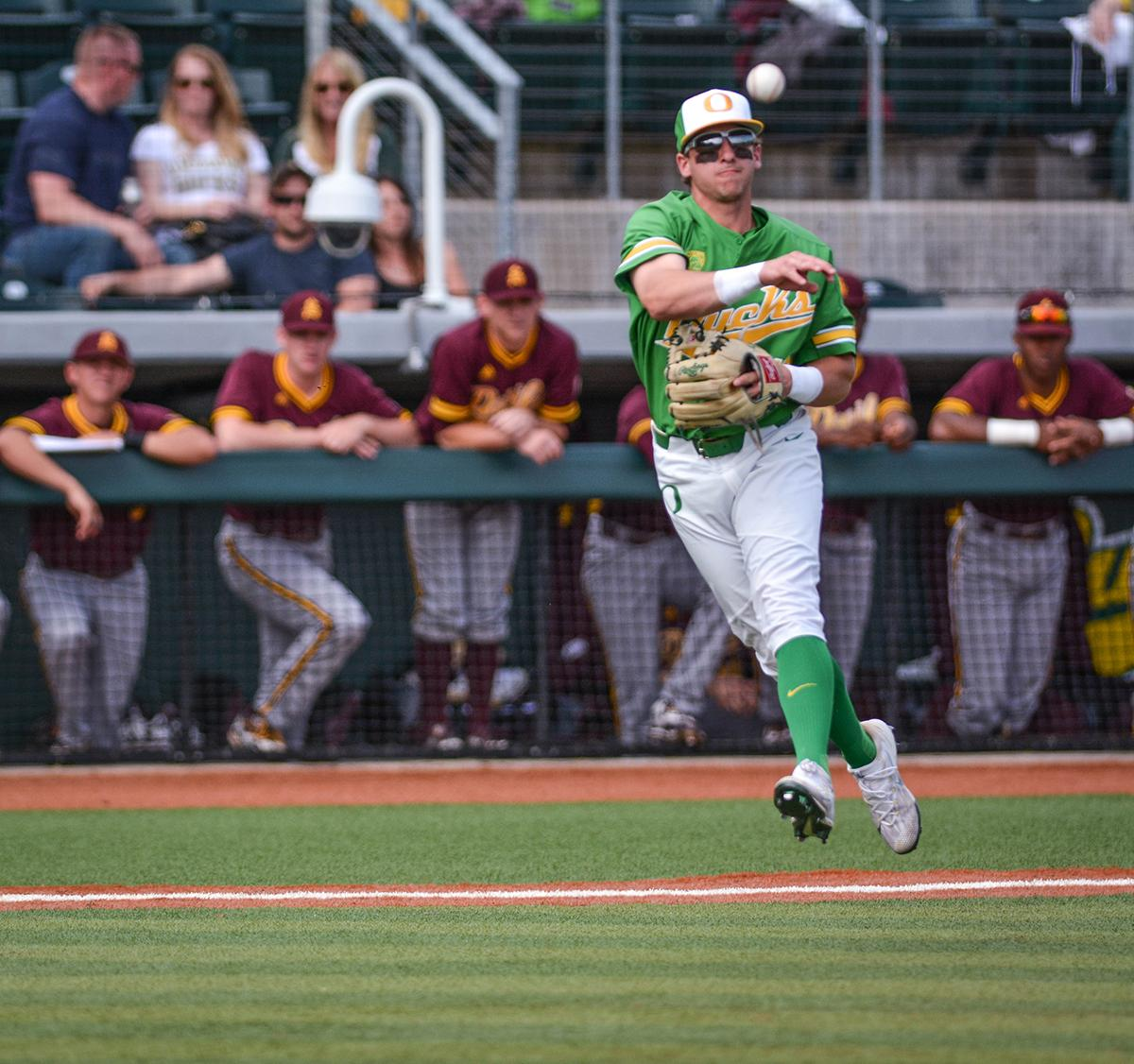 Ducks infielder Spencer Steer (#13) fires the ball from third base to first base in an attempt to get the runner out. Despite a late comeback, the Ducks fall to Arizona State Sun Devils 4-3 in the second game of a three-game series. Photo by Jacob Smith, Oregon News Lab
