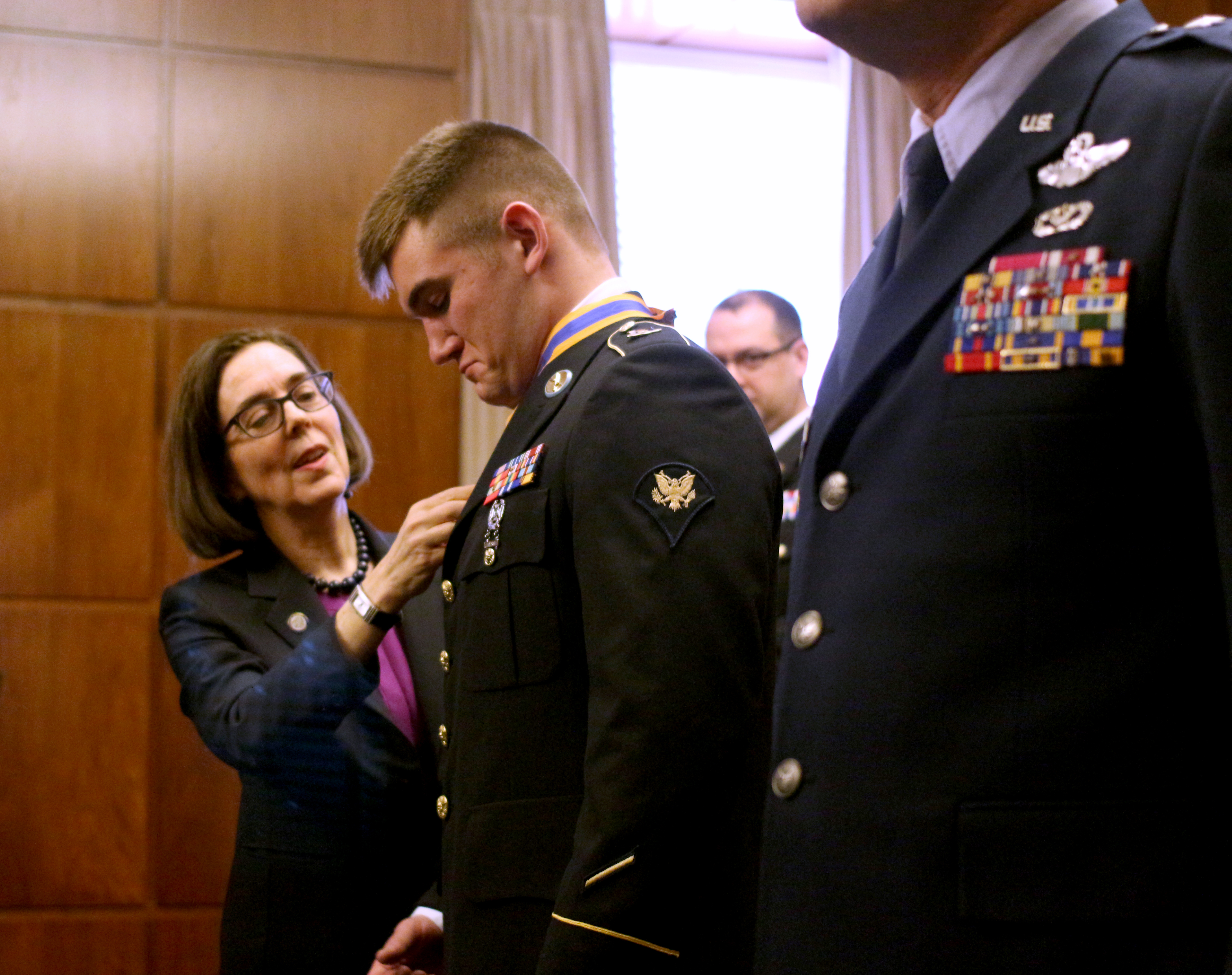 Gov. Kate Brown speaks with Alek Skarlatos after Skarlatos was awarded the Oregon Distinguished Service Award on Wednesday, Feb. 17, 2016 in Salem, Ore. Brown presented the Oregon Distinguished Service Medal to Skarlatos, the Oregon National Guard specialist who helped subdue a heavily armed gunman on a Paris-bound train last year.  (Gordon Friedman/Statesman-Journal via AP) MANDATORY CREDIT