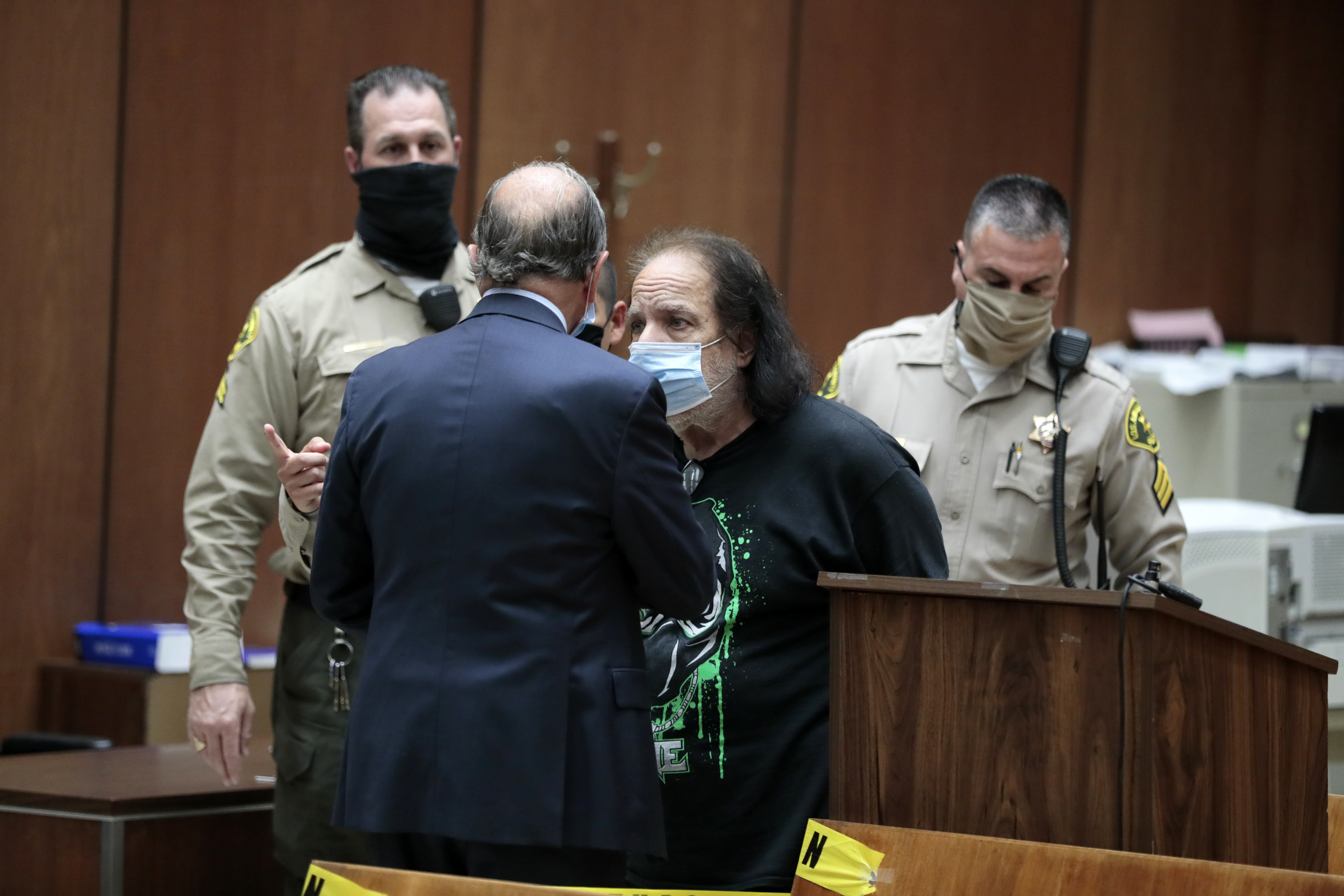 Adult film star Ron Jeremy, center, speaks to his attorney Stuart Goldfarb, during his first appearance at Los Angeles Superior Court in Los Angeles on Tuesday, June 23, 2020. Los Angeles County prosecutors say Jeremy has been charged with raping three women and sexually assaulting a fourth. (Robert Gauthier/Los Angeles Times via AP, Pool)