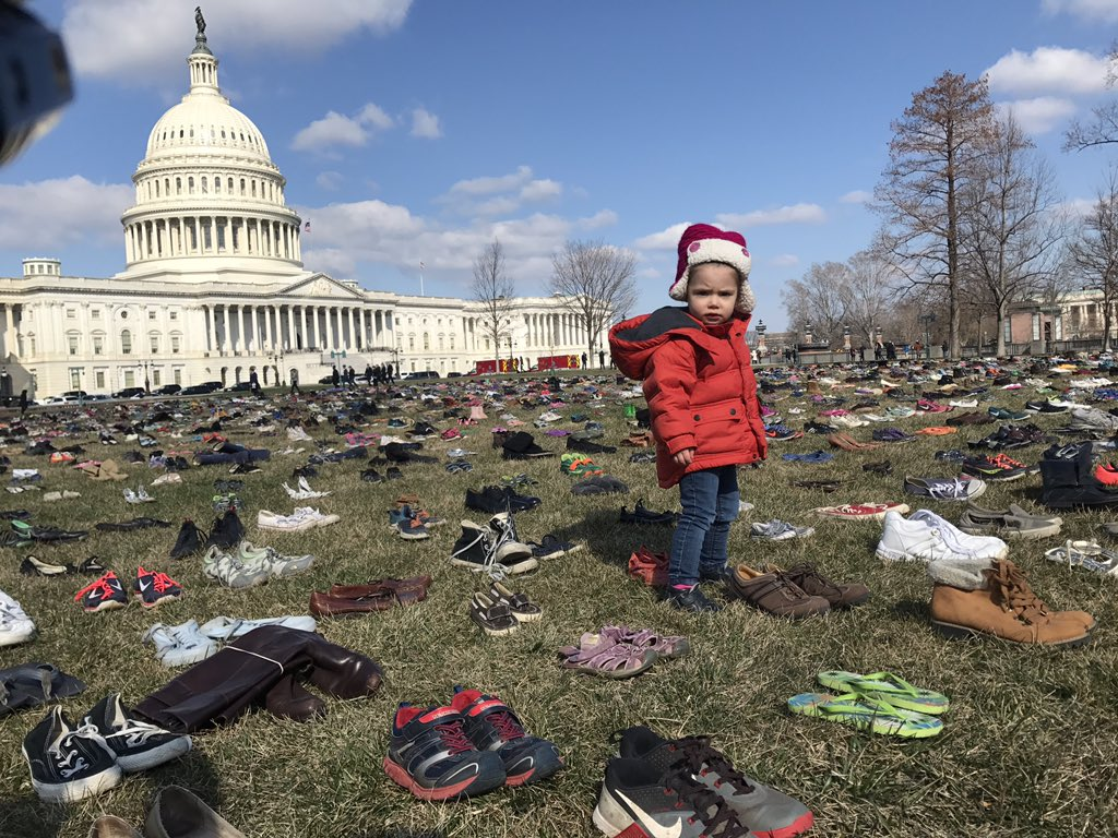 Gun control activists lay 7,000 pairs of shoes on the Capitol lawn on Tues., March 13, 2018, in honor of the children killed by guns since the 2012 Sandy Hook school shooting. (Caroline Patrickis, @CPatrickis / WJLA)