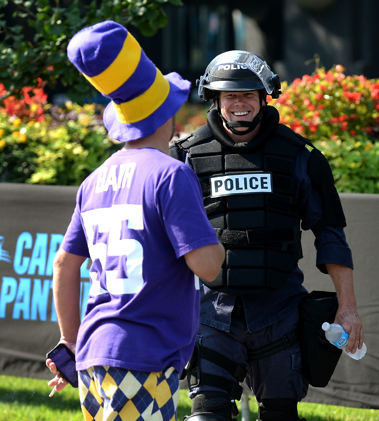 A Charlotte-Mecklenburg police officer laughs with a Minnesota Vikings fan near an entrance area at Bank of America Stadium, where people were protesting, in Charlotte, N.C., Sunday, Sept. 25, 2016. The Carolina Panthers hosted an NFL football game with the Vikings at the stadium. When the national anthem was played, the protesters all dropped to one knee as many NFL players have been doing for weeks to call attention to issues, including police shootings. (Diedra Laird/The Charlotte Observer via AP)