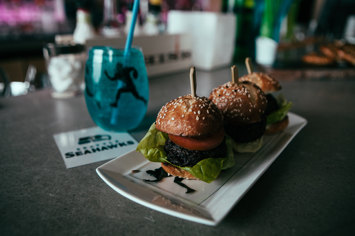 "Art Restaurant inside the Four Seasons hotel in Downtown Seattle is serving a Seahawks inspired spread which includes ""Seagal's"" crudité, ""1984"" warm pretzels, ""Legion of Boom"" wings, ""Clink"" cheese sauce nachos, ""Touchback"" Seattle dogs, ""Feed the Beast"" pizza, and ""137.6 decibel"" fried chicken and fries. (Joshua Lewis / Seattle Refined)"