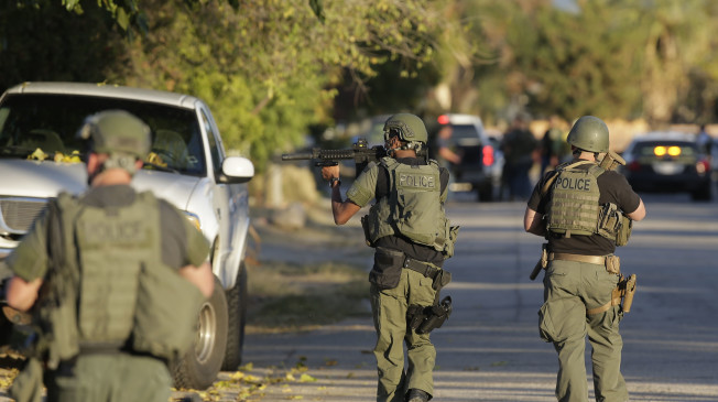 Law enforcement search for a suspect in a mass shooting at a Southern California social services center on Wednesday, Dec. 2, 2015, in San Bernardino, Calif. One or more gunmen opened fire Wednesday at a California center that serves people with developmental disabilities, shooting several people as others locked themselves in their offices, desperately waiting to be rescued by police, witnesses and authorities said. (AP Photo/Chris Carlson)