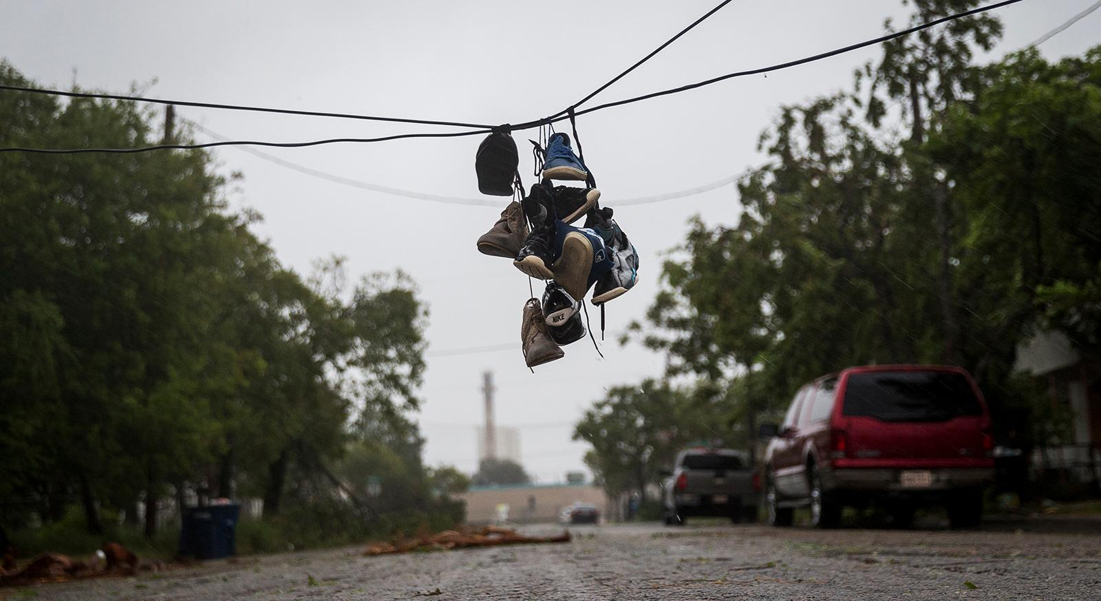 Shoes tied to a power line hang near a street after winds from Hurricane Harvey brought down a power pole in Corpus Christi, Texas, on Friday, Aug. 25, 2017. Hurricane Harvey smashed into Texas late Friday, lashing a wide swath of the Gulf Coast with strong winds and torrential rain from the fiercest hurricane to hit the U.S. in more than a decade.  (Nick Wagner/Austin American-Statesman via AP)