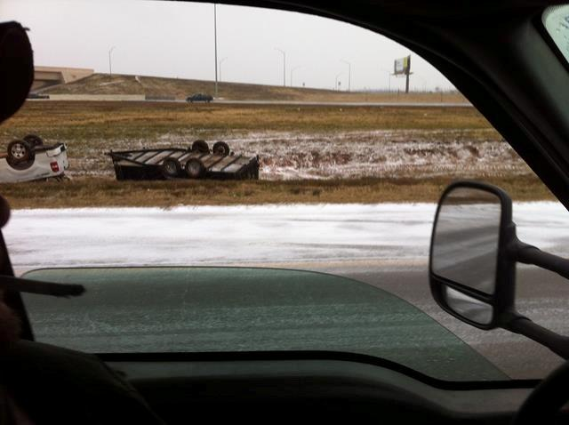 A truck and its trailer rest flipped upside just off an Oklahoma City interstate.