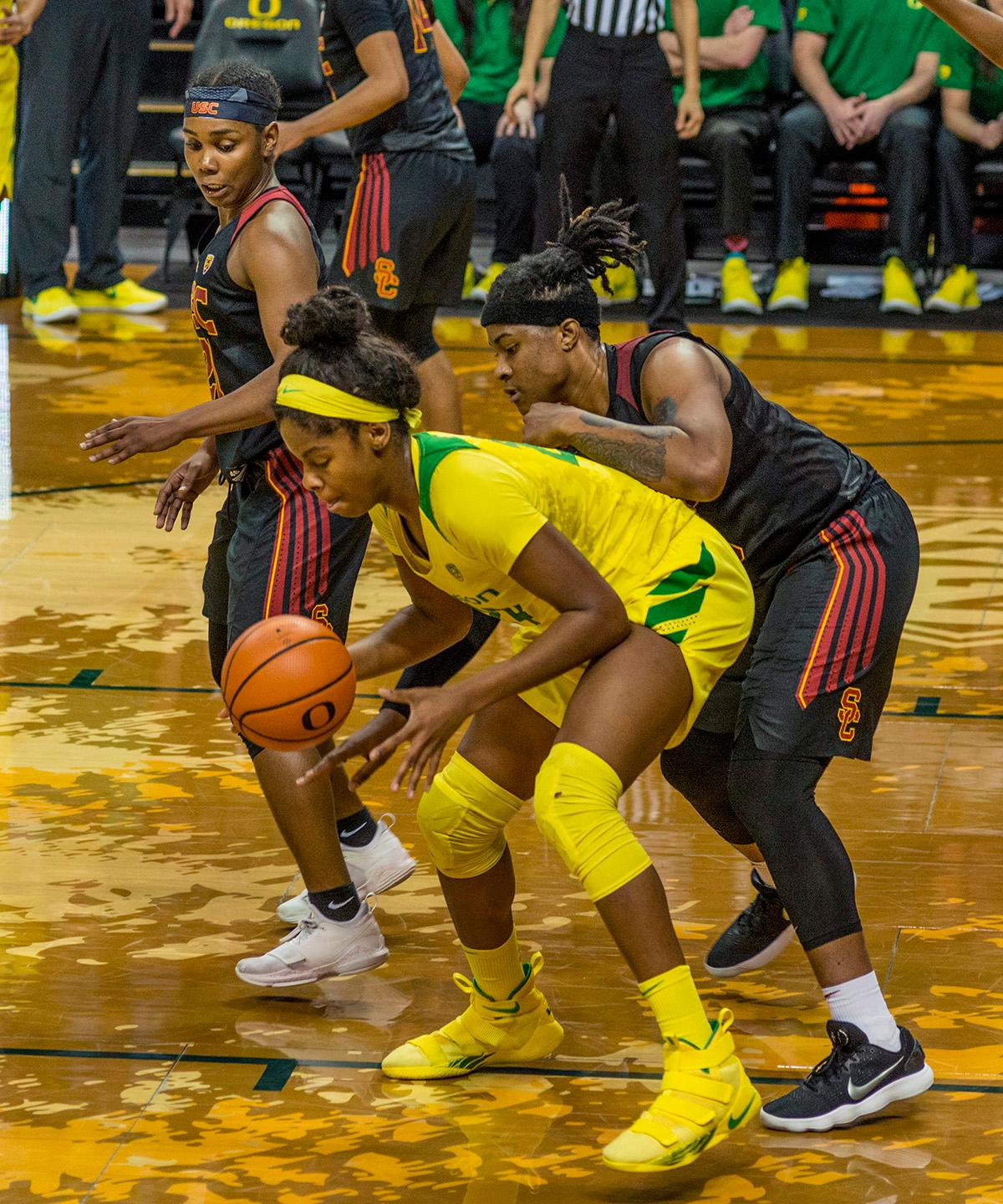 Oregon Ducks Ruthy Hebard (#24, with ball) plays keep away from USC Kristen Simon (#35). The Oregon Ducks defeated the USC Trojans 80-74 on Friday at Matthew Knight Arena in a game that went into double overtime. Lexi Bando sealed the Ducks' victory by scoring a three-pointer in the closing of the game. Ruthy Hebard set a new NCAA record of 30 consecutive field goals over three games, the old record being 28. Ruthy Hebard got a double-double with 27 points and 10 rebounds, Mallory McGwire also had 10 rebounds. The Ducks had four players in double digits: Ruthy Hebard with 27; Maite Cazorla with 17; Sabrina Ionescu with 15; and Lexi Bando with 11. The Ducks are now 24-4, 13-2 in the Pac-12, and are tied for first with Stanford. Photo by Dan Morrison, Oregon News Lab