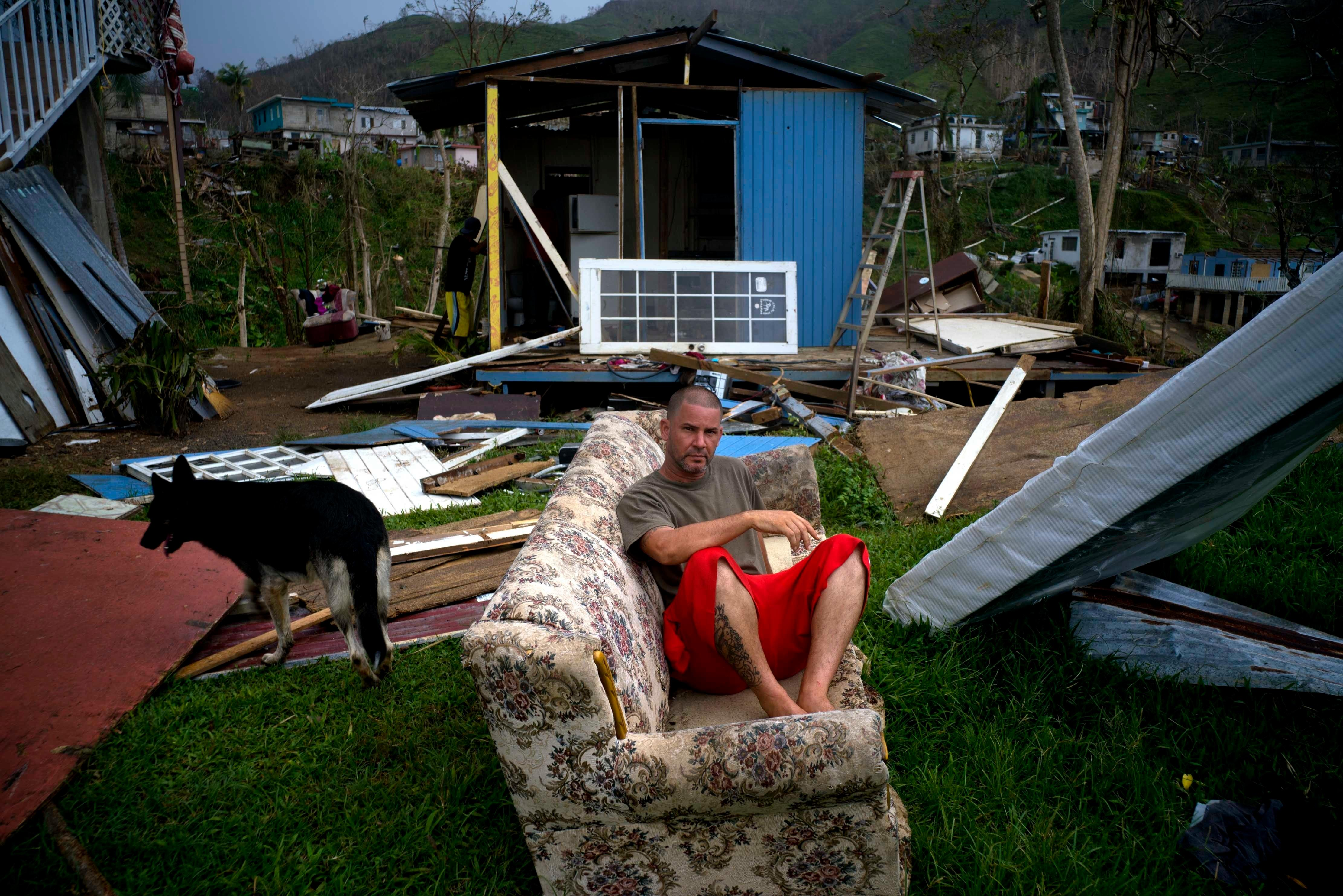 "CORRECTS FROM MORAVIS TO MOROVIS- Angel Rodriguez poses next to his belongings in front of his house, destroyed by Hurricane Maria, in the San Lorenzo neighborhood of Morovis, Puerto Rico, Saturday, Sept. 30, 2017. Rodriguez said that it rained and rained. ""I was really afraid on the night of the hurricane. But the important thing is to be alive,"" he said. (AP Photo/Ramon Espinosa)"
