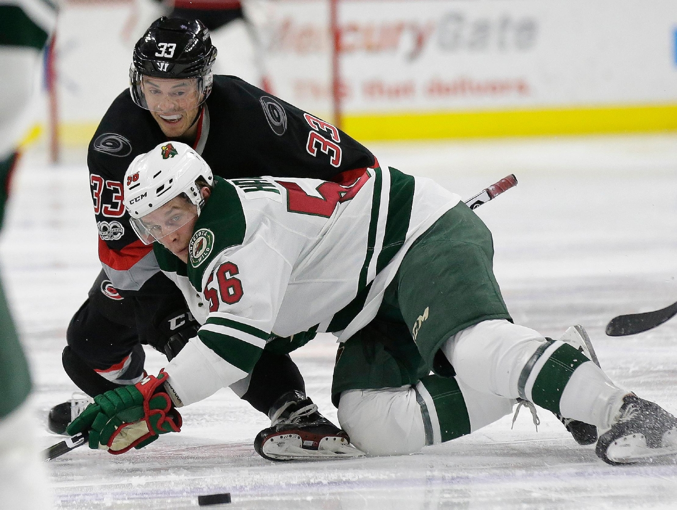Carolina Hurricanes' Derek Ryan (33) and Minnesota Wild's Erik Haula (56), of Finland, struggle for possession of the puck during the second period of an NHL hockey game in Raleigh, N.C., Thursday, March 16, 2017. (AP Photo/Gerry Broome)