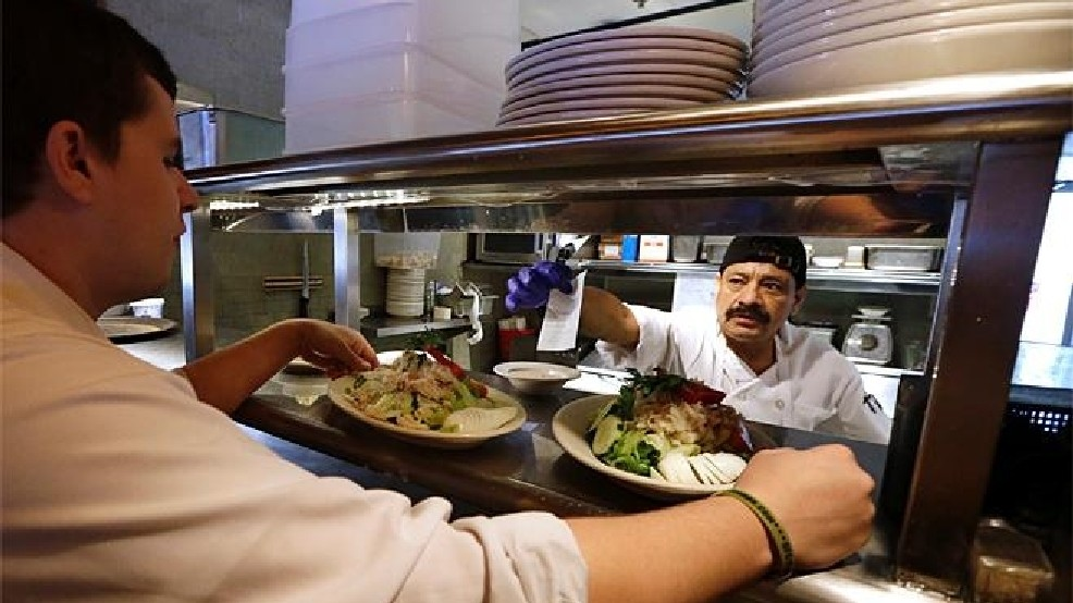 Restaurant workers in this file photo serve up food in Seattle where the city's $15 minimum wage is being partially blamed by a restaurant ownership group for the company's bankruptcy filing. (photo: KOMO News)