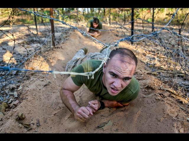 U.S. Marine Corps Lance Cpl. Trevor Smitherman crawls under concertina wire on an obstacle course during a weeklong squad competition on Robertson Barracks in Darwin, Australia, June 2, 2014.