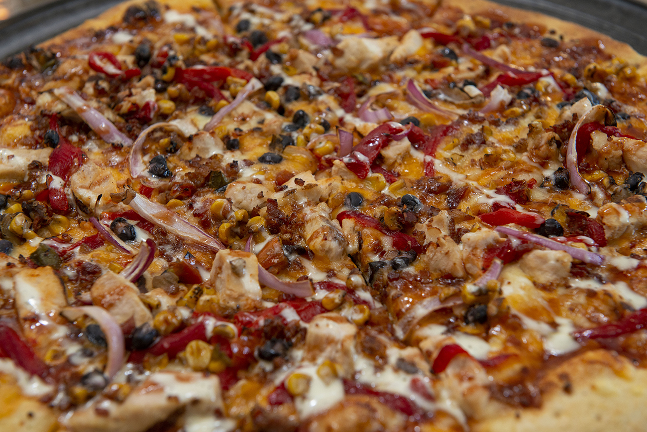 The Ohio BBQ Pizza: BBQ sauce base, cheddar cheese, grilled chicken, bacon, roasted red pepper, red onion, corn salsa, black beans, BBQ, and ranch drizzle{ }/ Image: Joe Simon // Published: 3.2.21