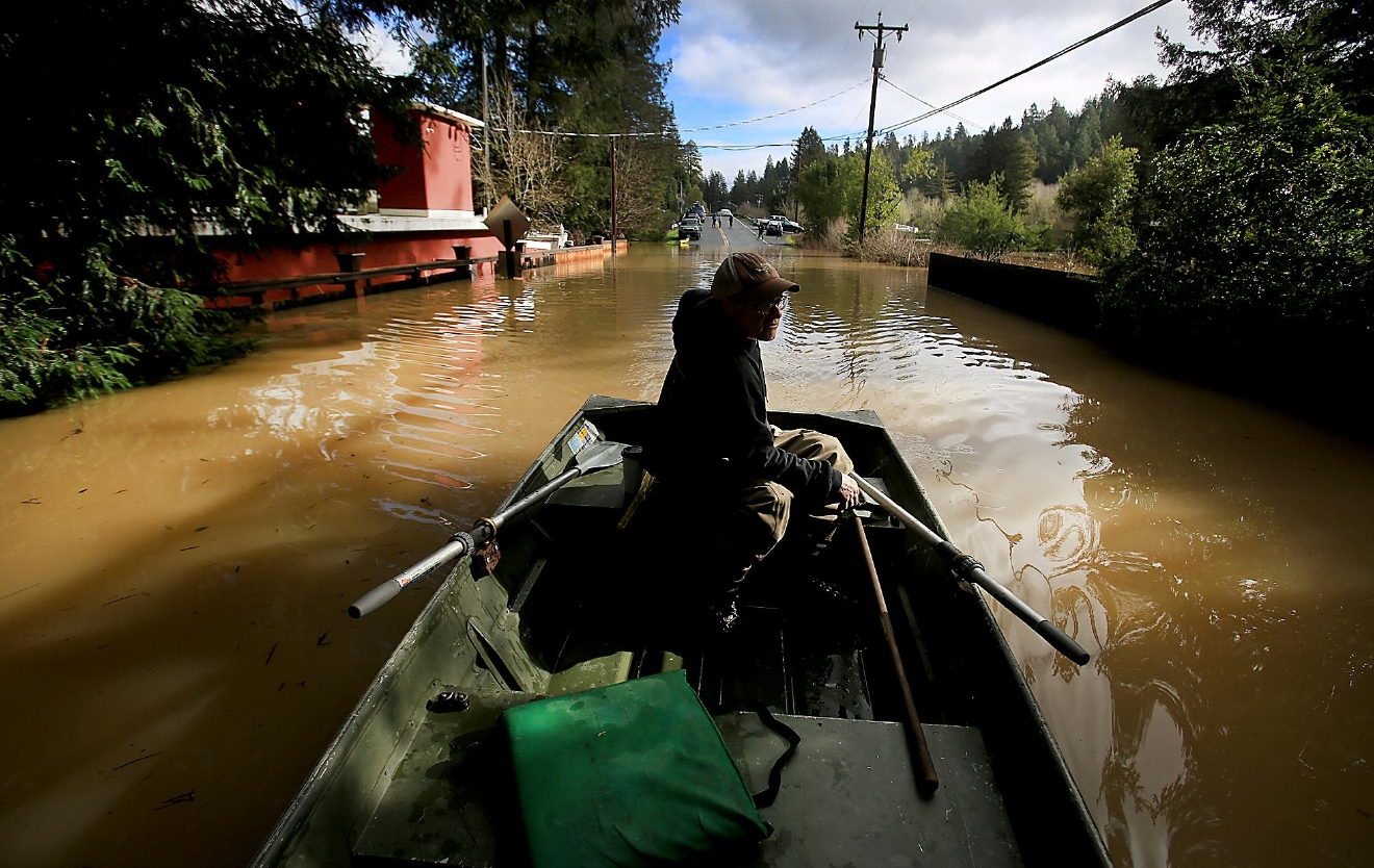 Bruce MacDonnell paddles over a flooded road as the Russian River crested in Guerneville, Calif., on Wednesday Jan. 11, 2017.   Forecasters said precipitation would continue through Thursday,  (Kent Porter/The Press Democrat via AP)