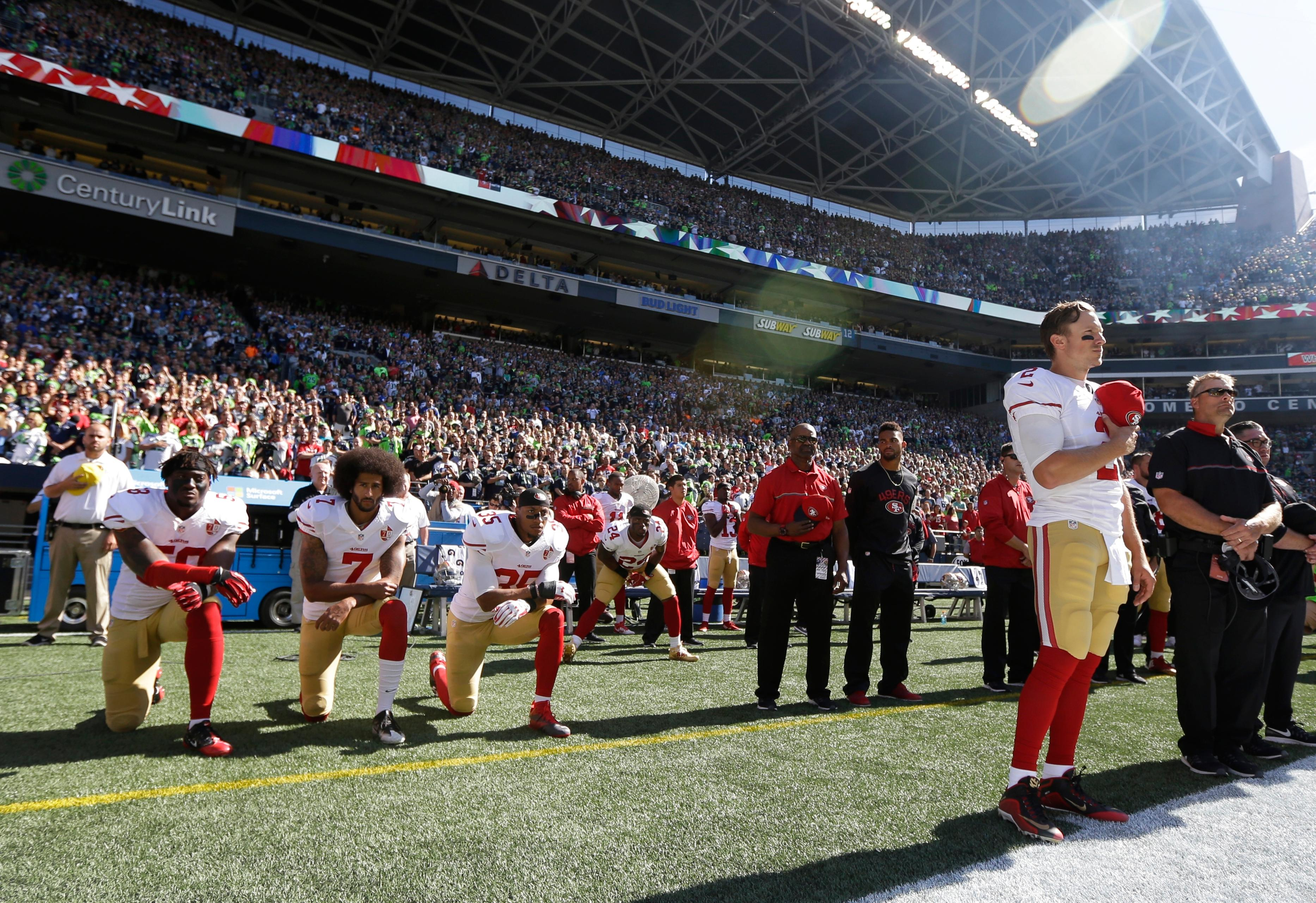 FILE - In this Sept. 25, 2016, file photo, San Francisco 49ers Blaine Gabbert, right, stands as Eli Harold (58), Colin Kaepernick (7) and Eric Reid (35) kneel during the national anthem before an NFL football game against the Seattle Seahawks in Seattle. {&amp;nbsp;}(AP Photo/Ted S. Warren, File)<p></p>