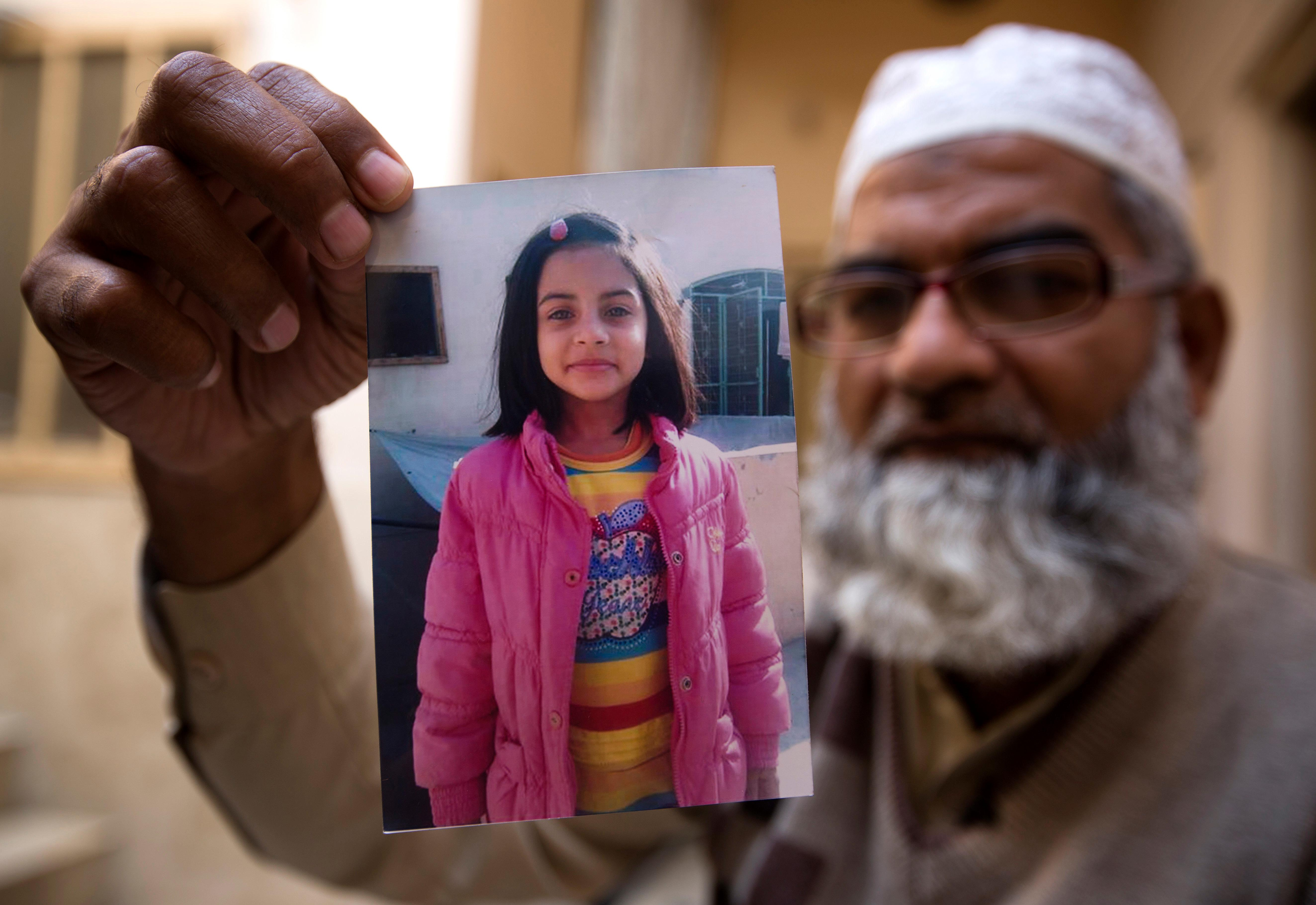 In this Thursday, Jan. 18, 2018 photo, Mohammed Amin shows a picture of his seven year-old daughter, Zainab Ansari in Kasur, Pakistan. (AP Photo/B.K. Bangash)