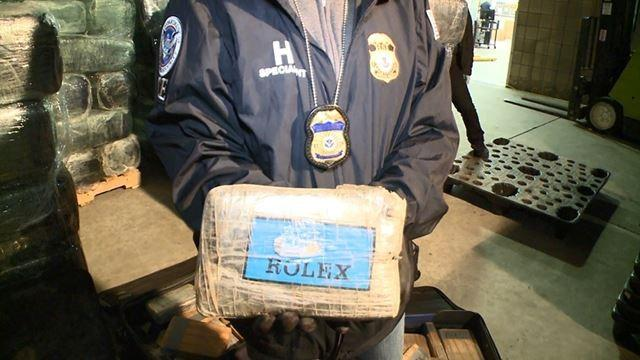 An agent shows off one of the packages with the name 'Rolex'.